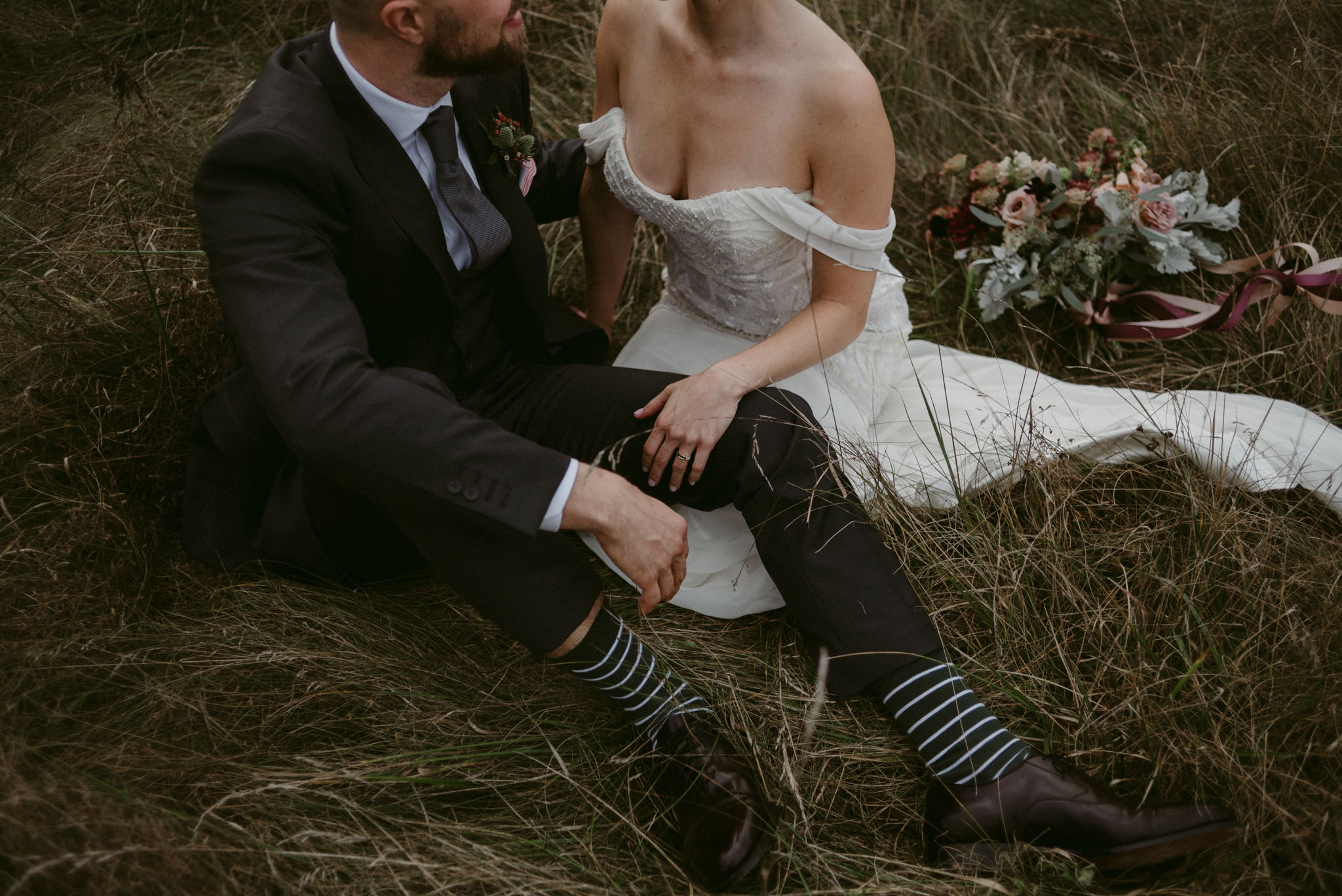 Bride and groom sitting in field