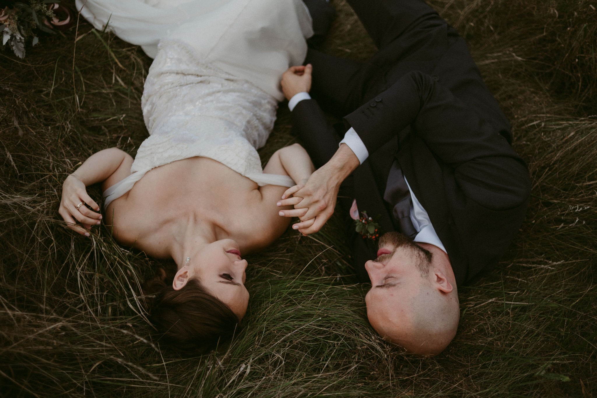 Bride and groom lying down side by side in field