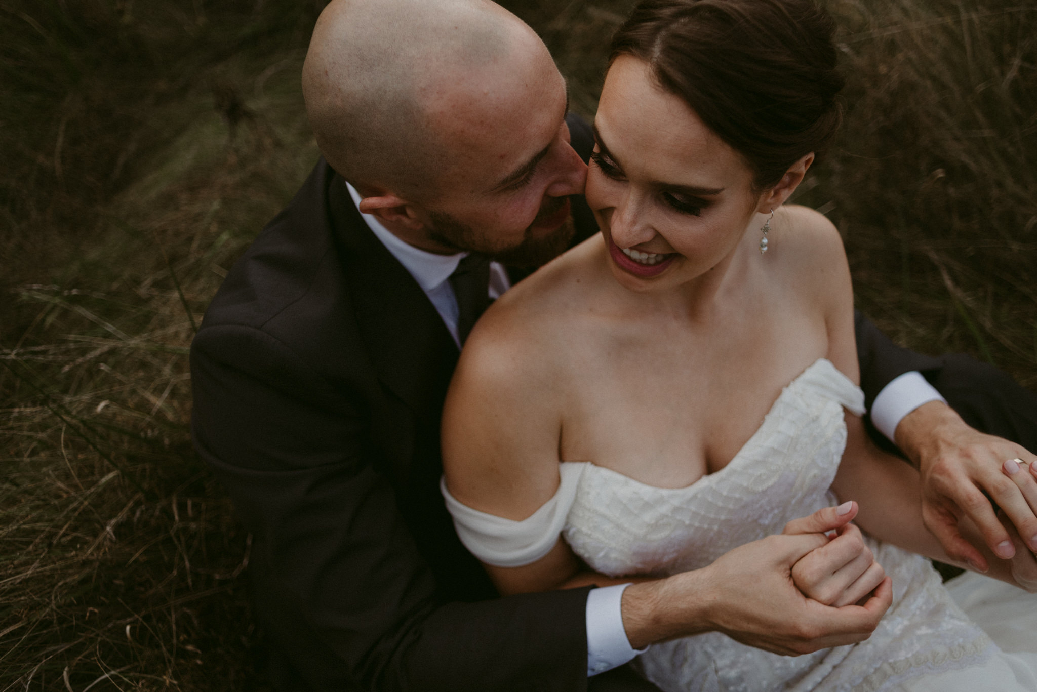 Bride cuddling into groom in field