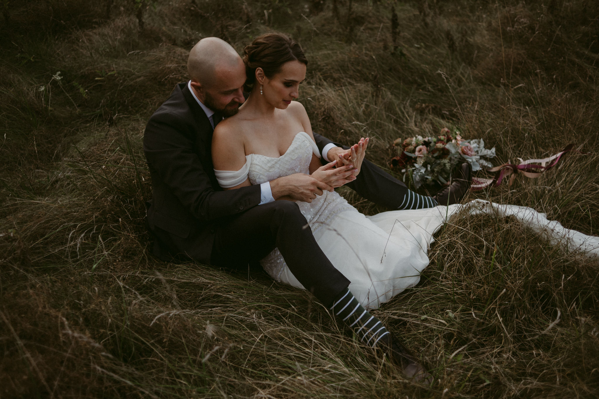 Bride sitting between groom's legs in field playing with each other's hands