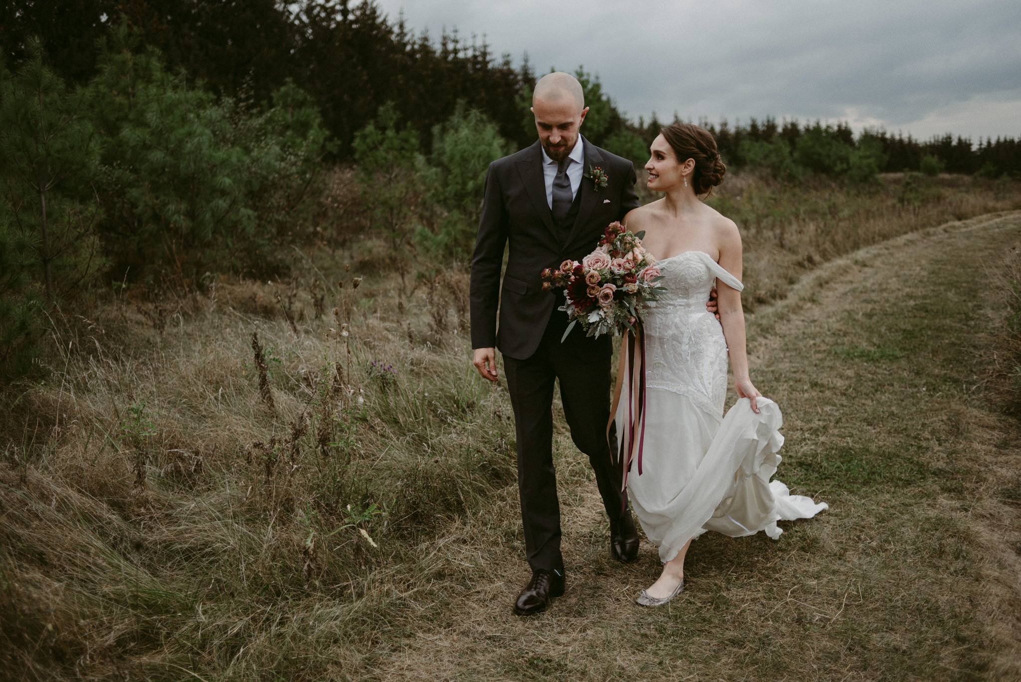 Bride and groom walking together in field