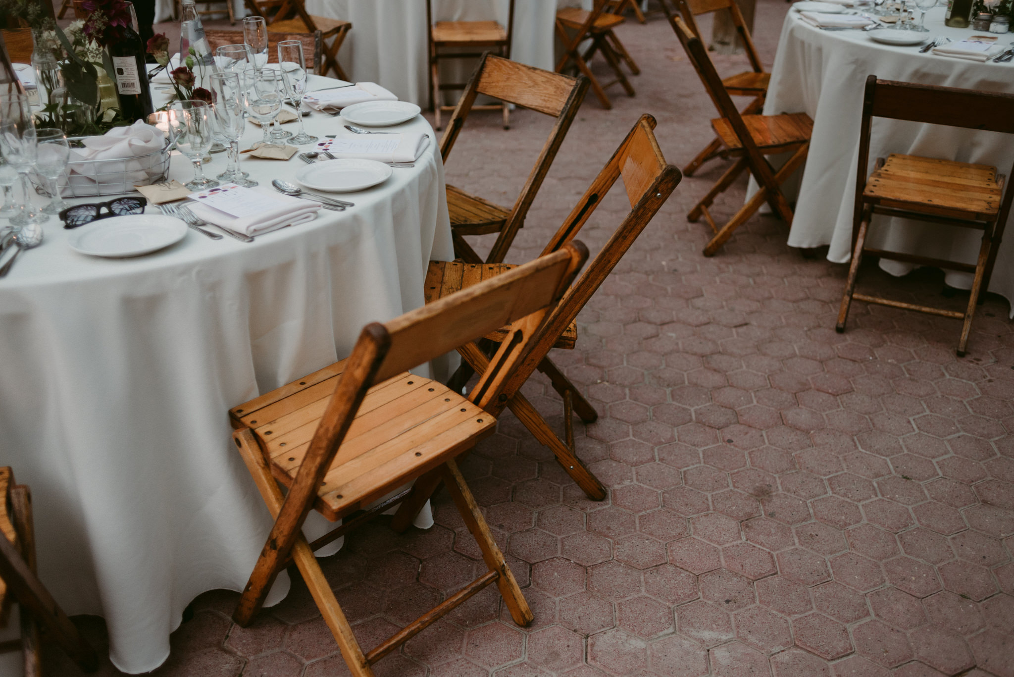 Round tables with white table clothes and wooden chairs
