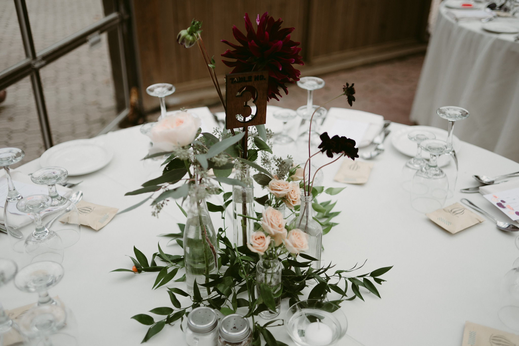 Flower and greenery centrepieces for wedding reception with wooden table number