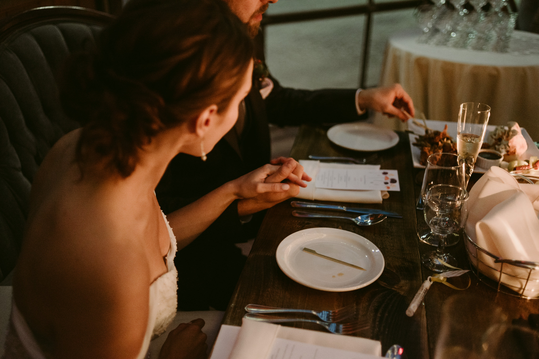 bride and groom holding hands at table during wedding reception