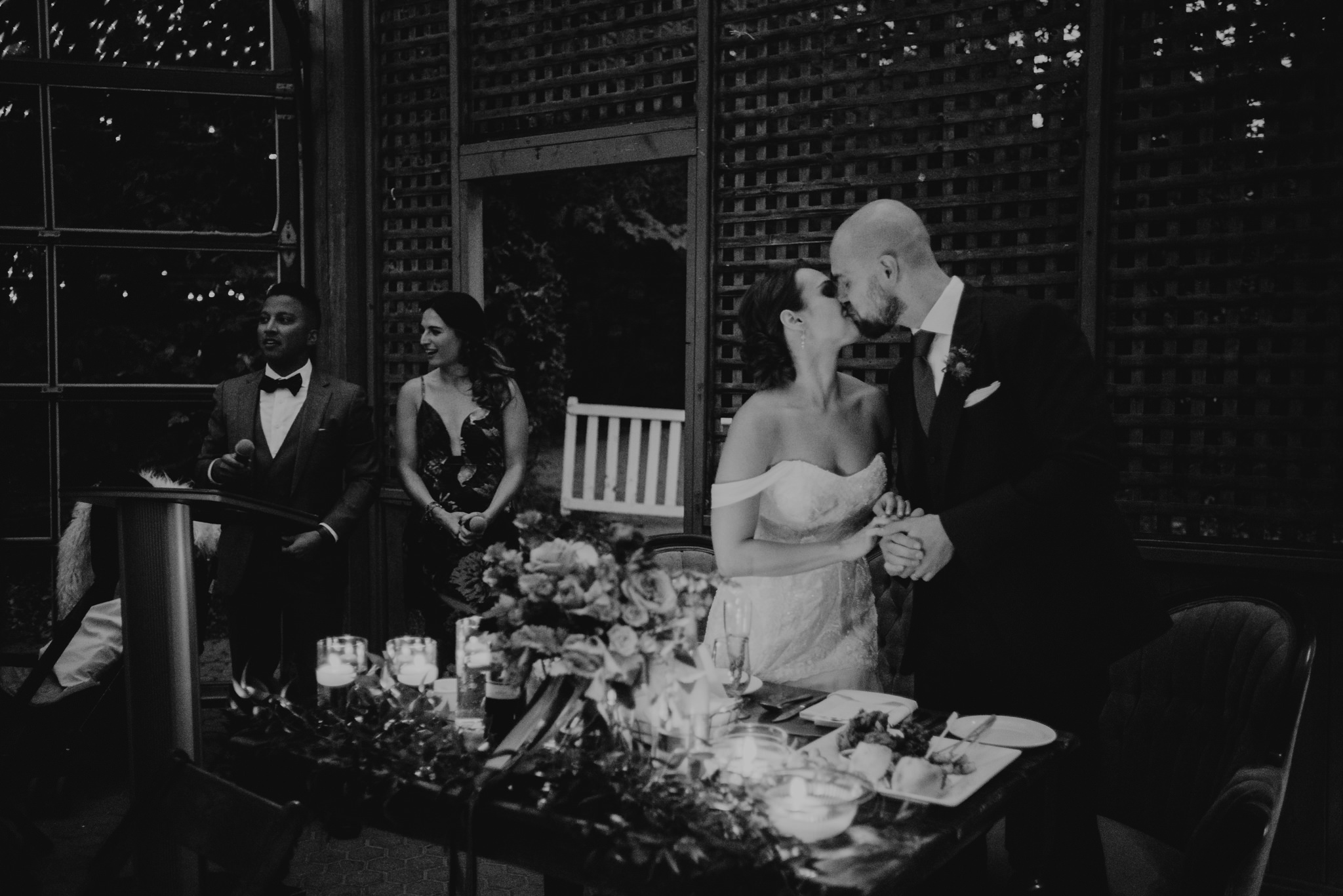 black and white of bride and groom kissing during wedding reception