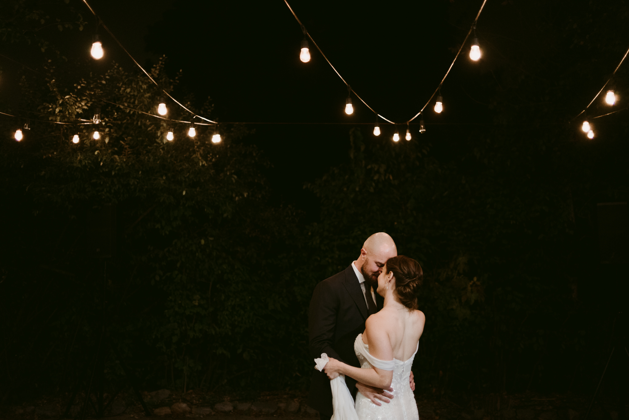Bride and groom dancing under string lights