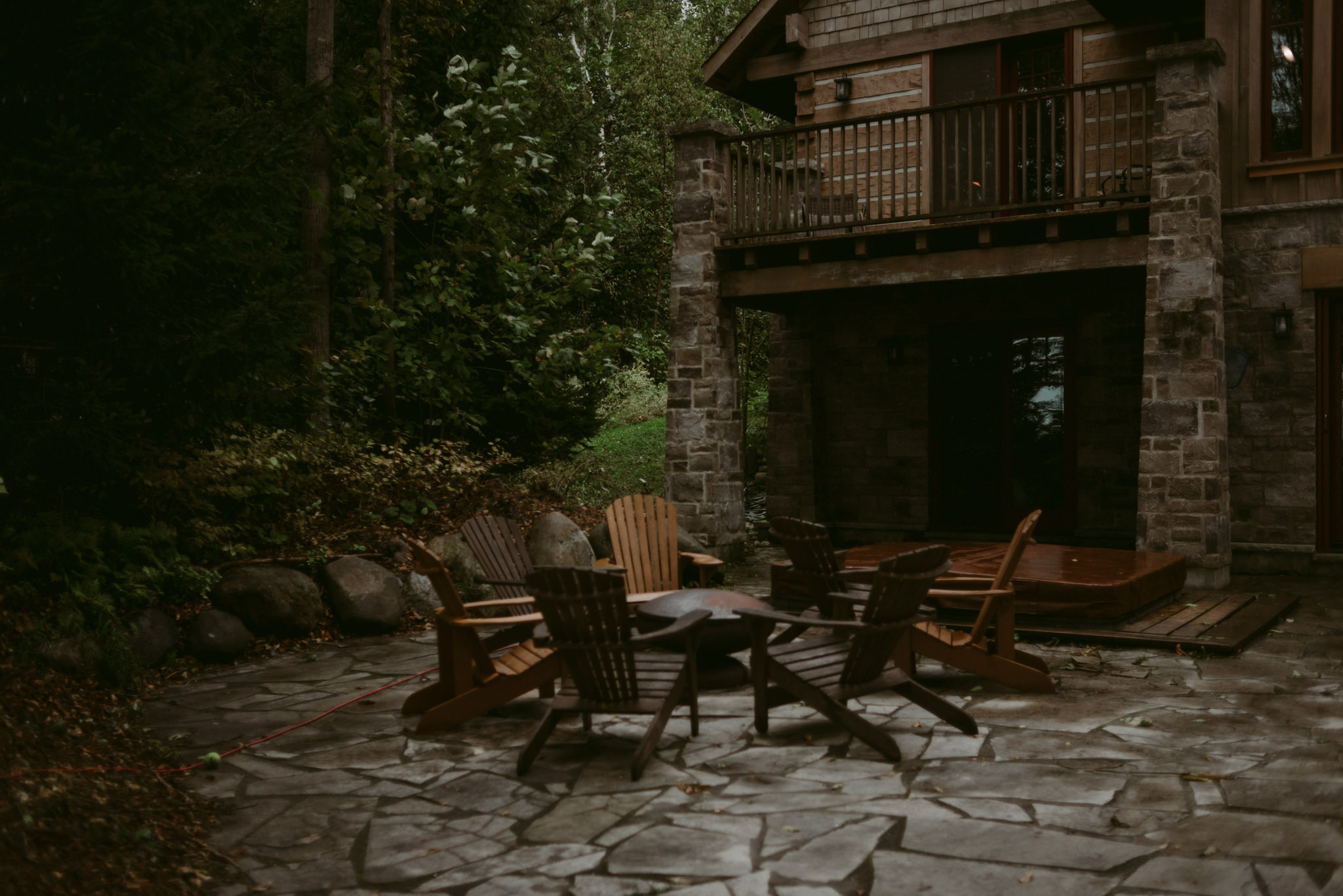 Adirondack chairs around fire pit at cottage