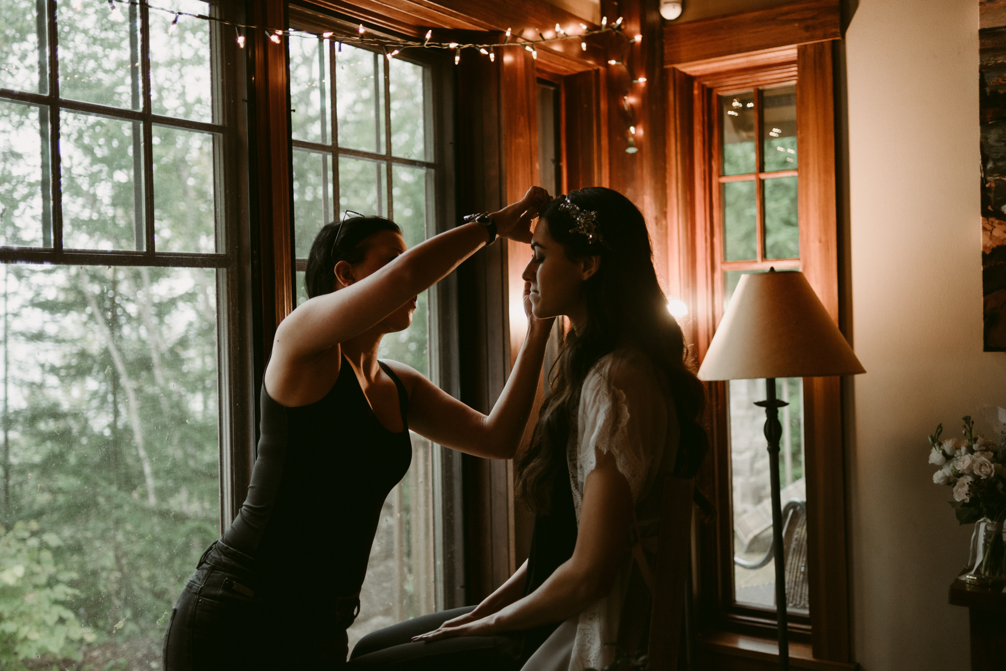 Bride getting makeup done by window at cottage