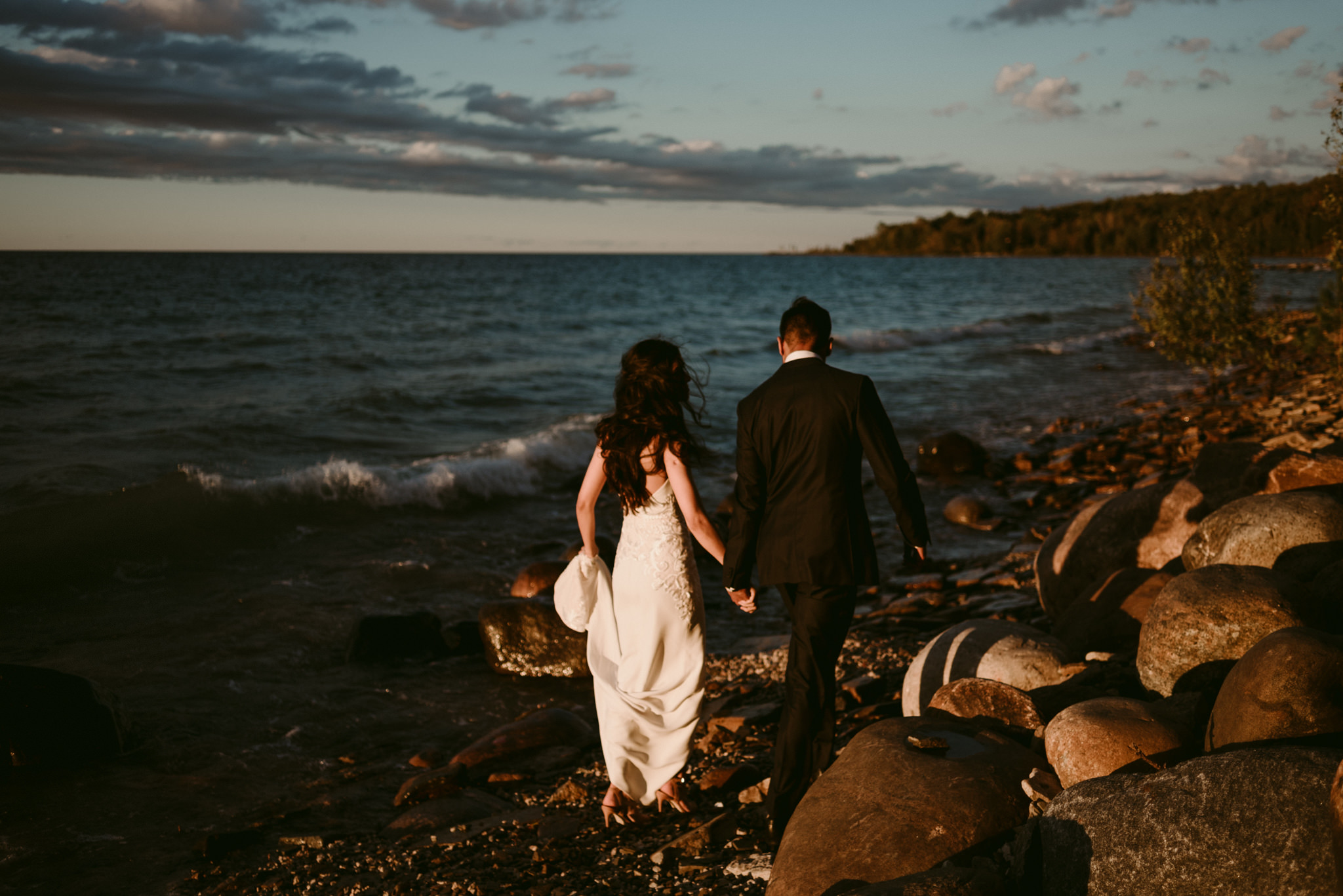 bride and groom walking on waterfront at sunset on georgian bay
