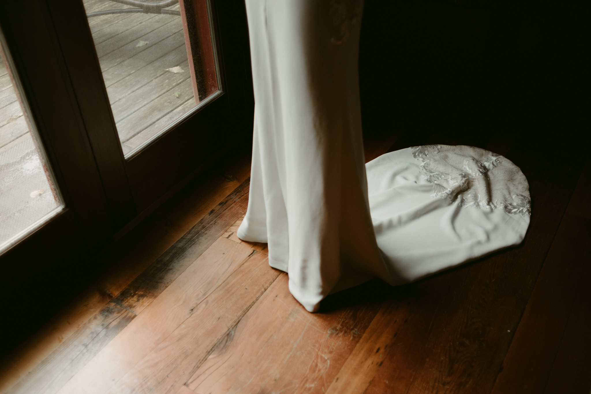 Bride wedding dress train on wood floor by door