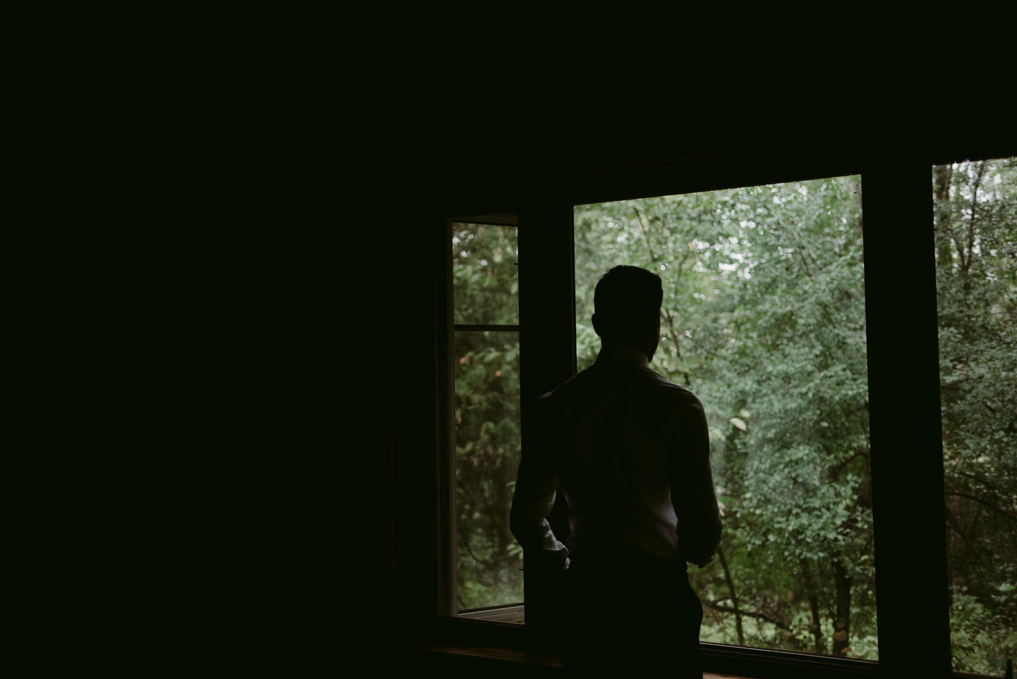 Groom standing and looking out window at forest in cottage