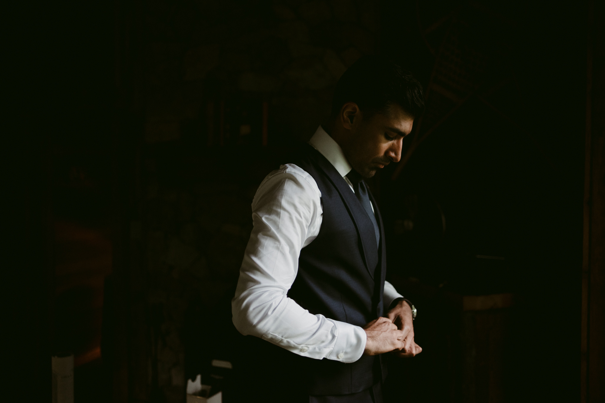 groom getting dressed and buttoning up vest in dark cottage