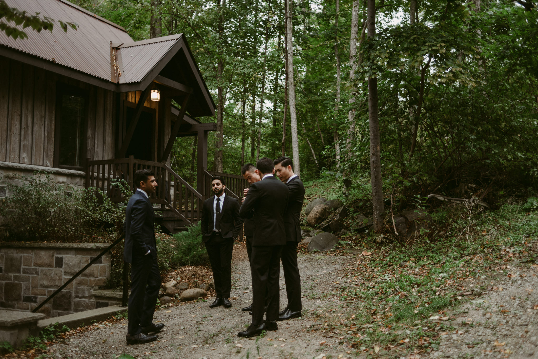Groomsmen standing outside cottage