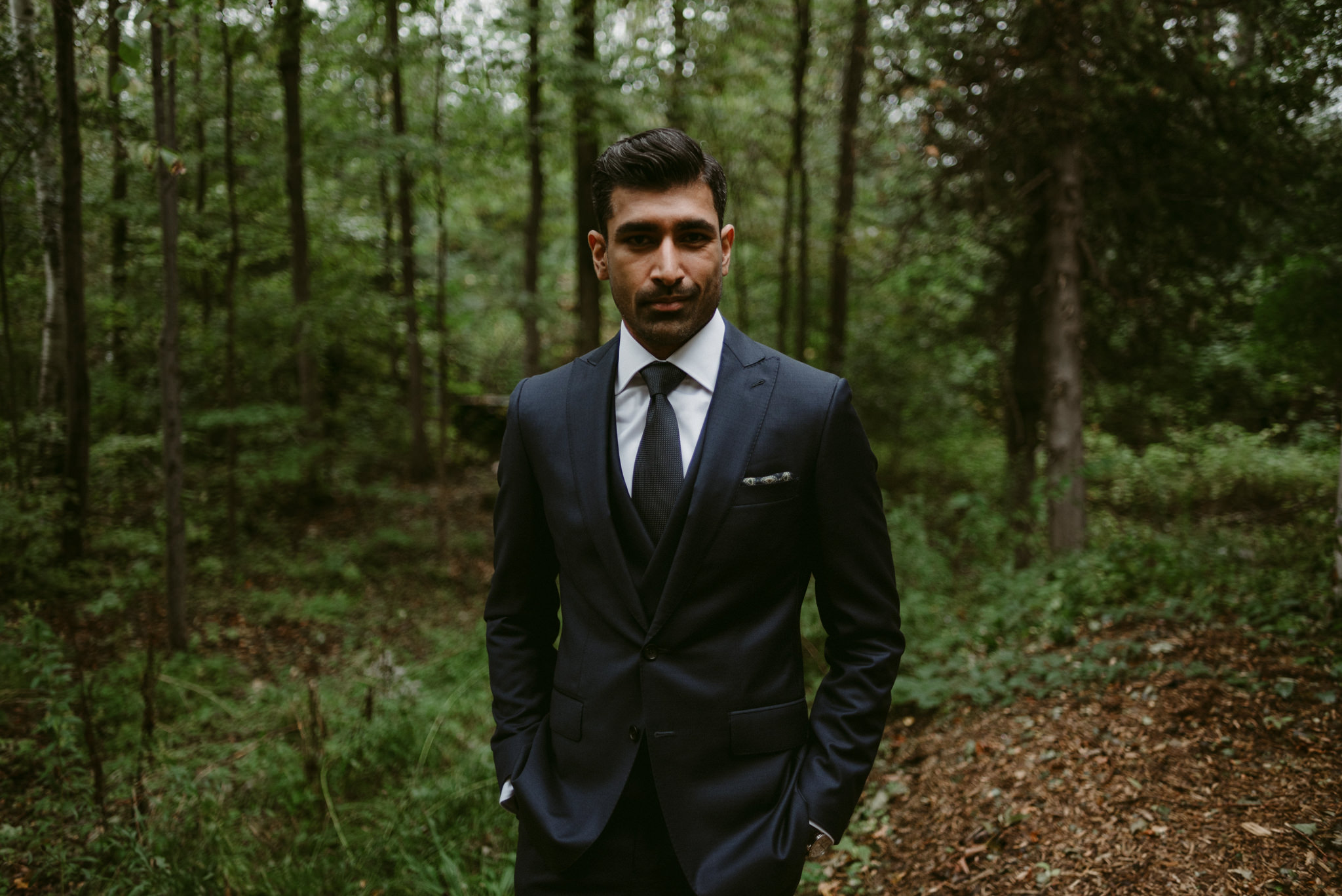 groom looking into camera and standing in forest