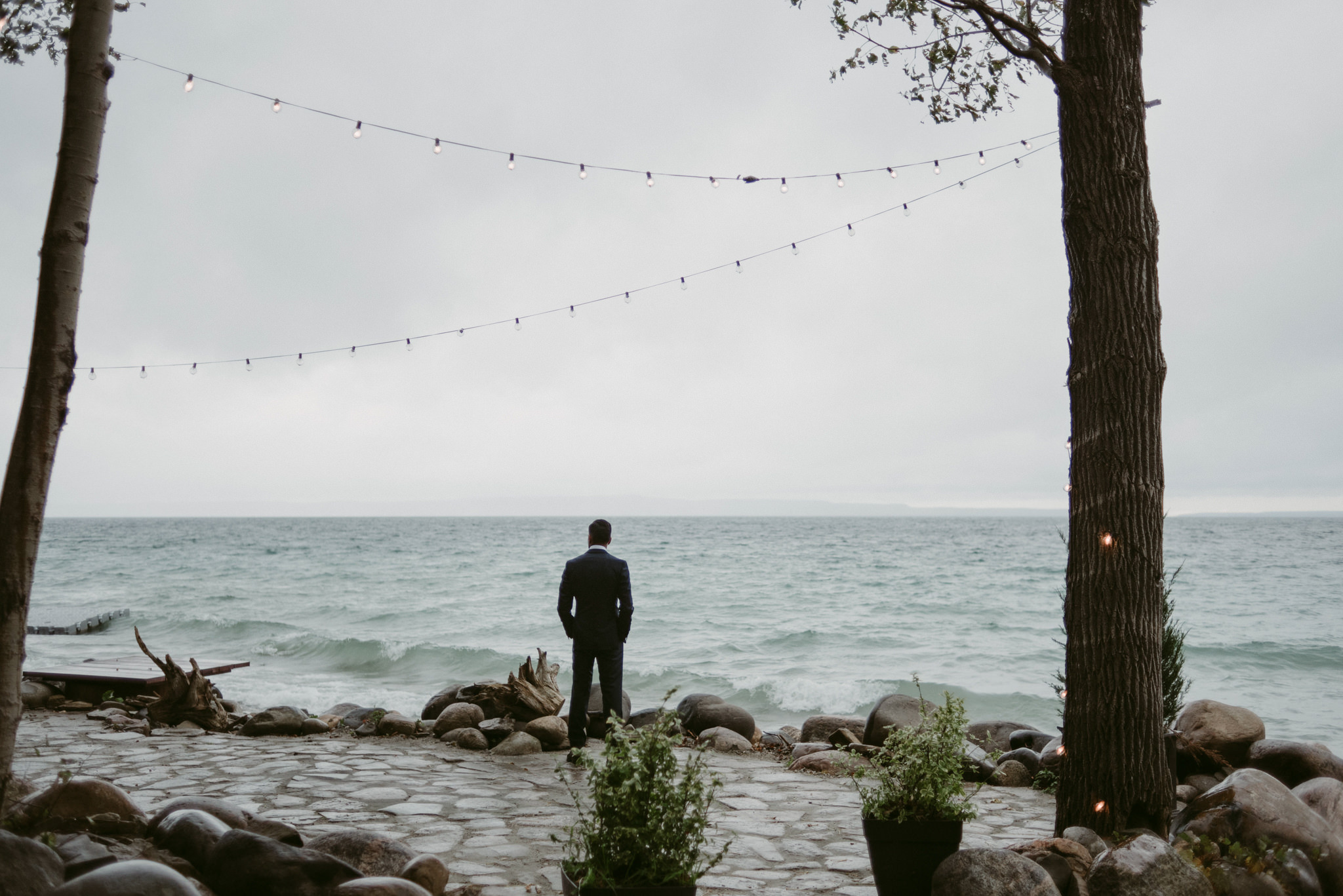 Groom looking out onto lake waiting for bride