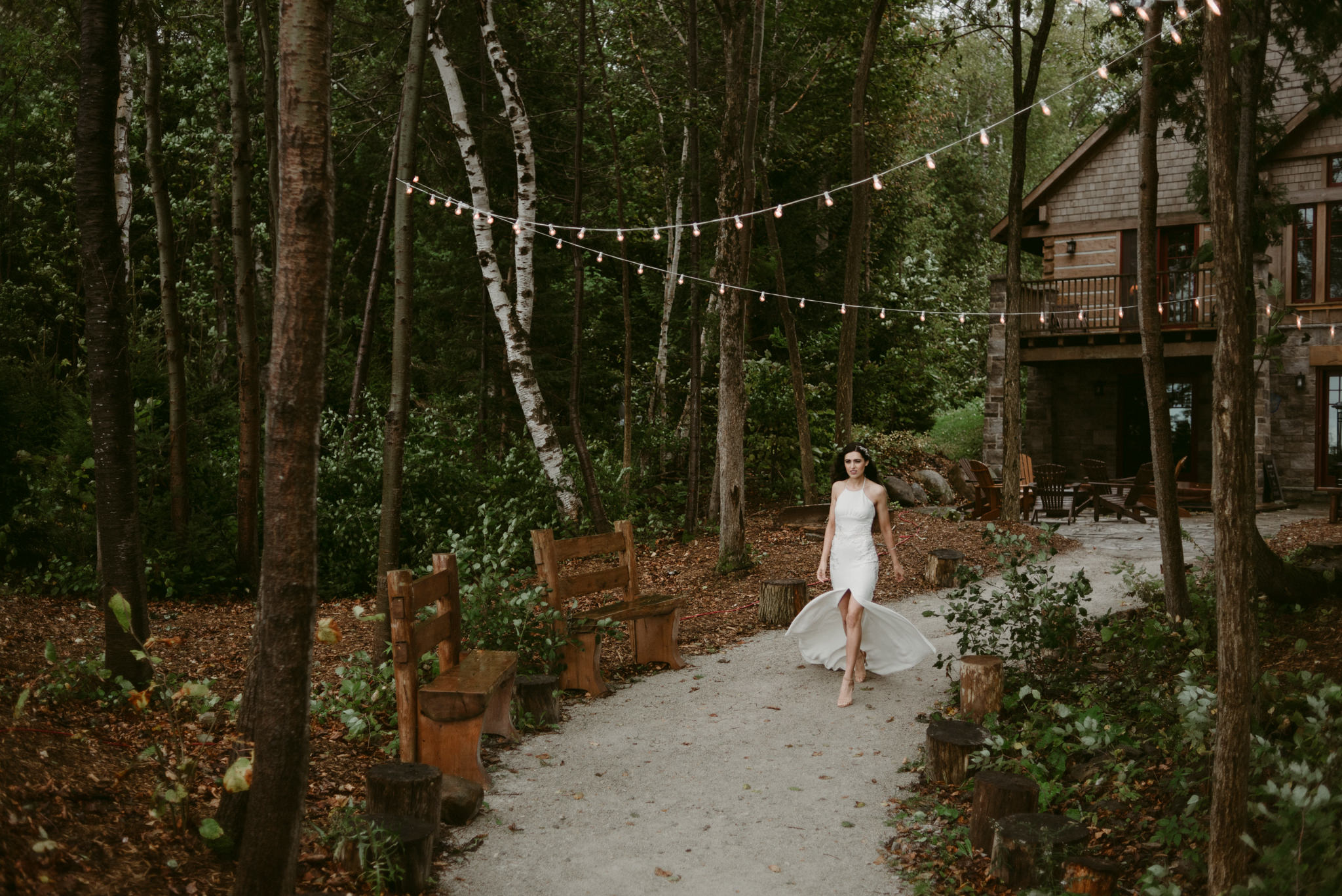 bride walking down path from cottage with string lights overhead