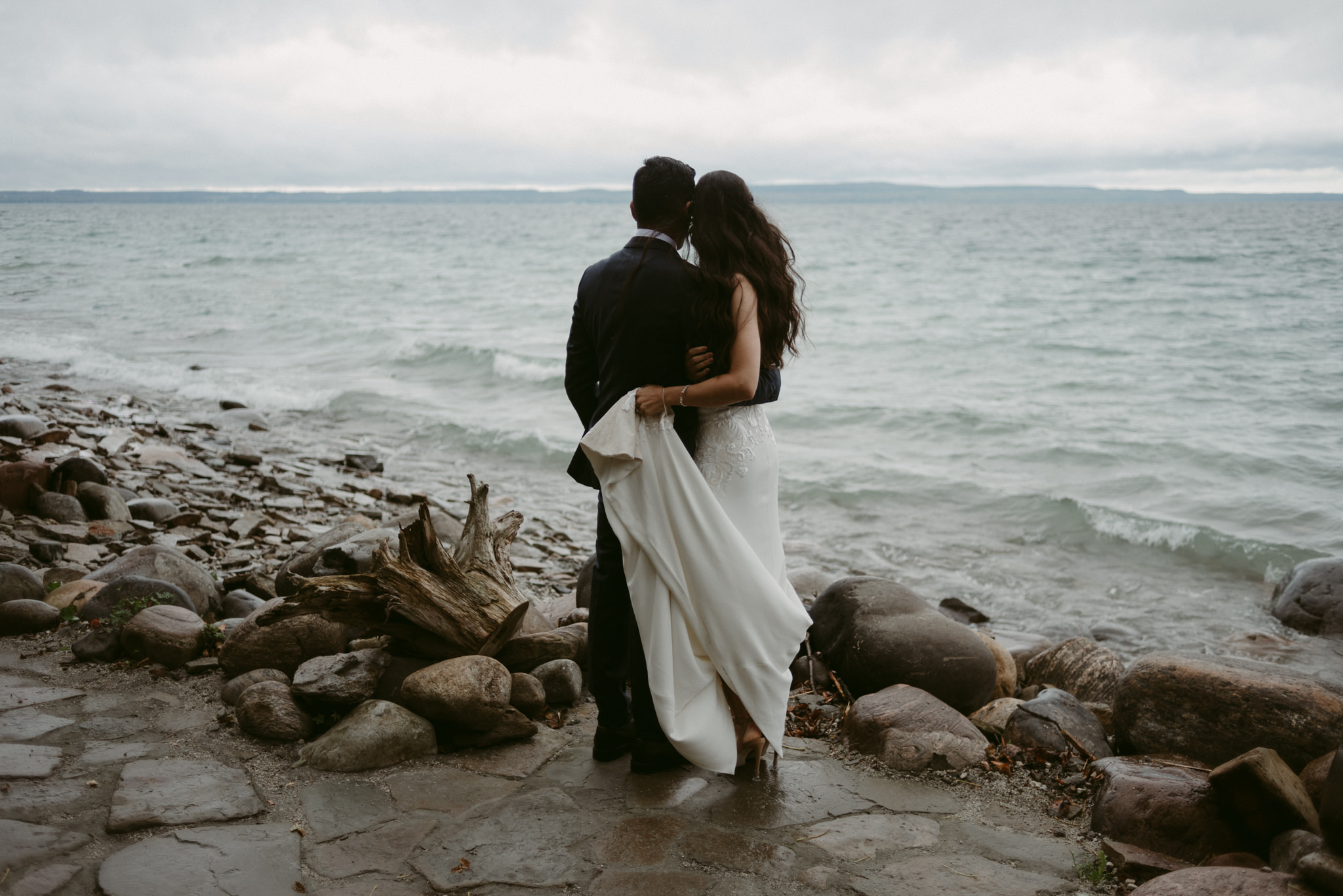 Bride and groom hugging and looking out onto water