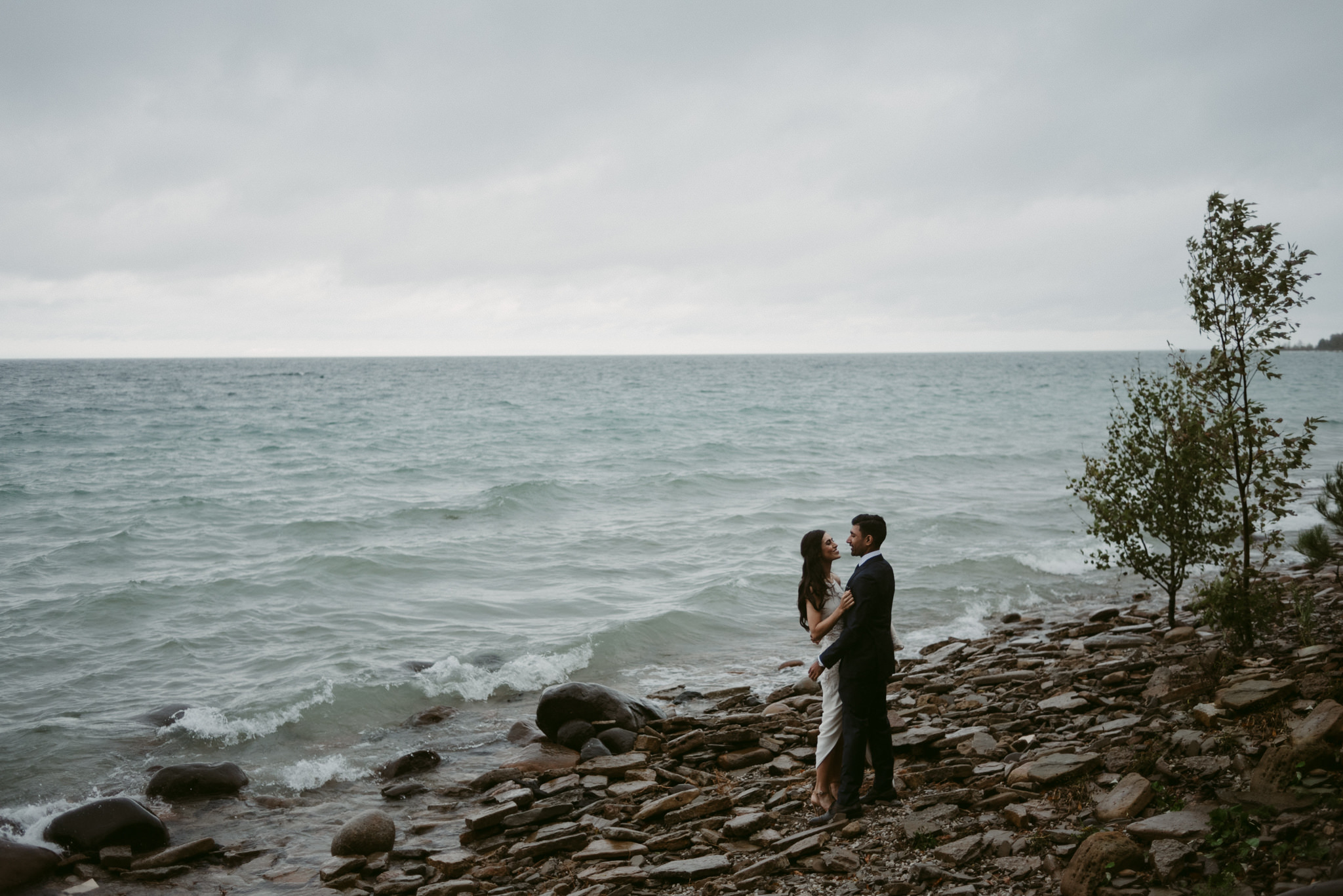 Bride and groom hugging on lakefront on stormy day