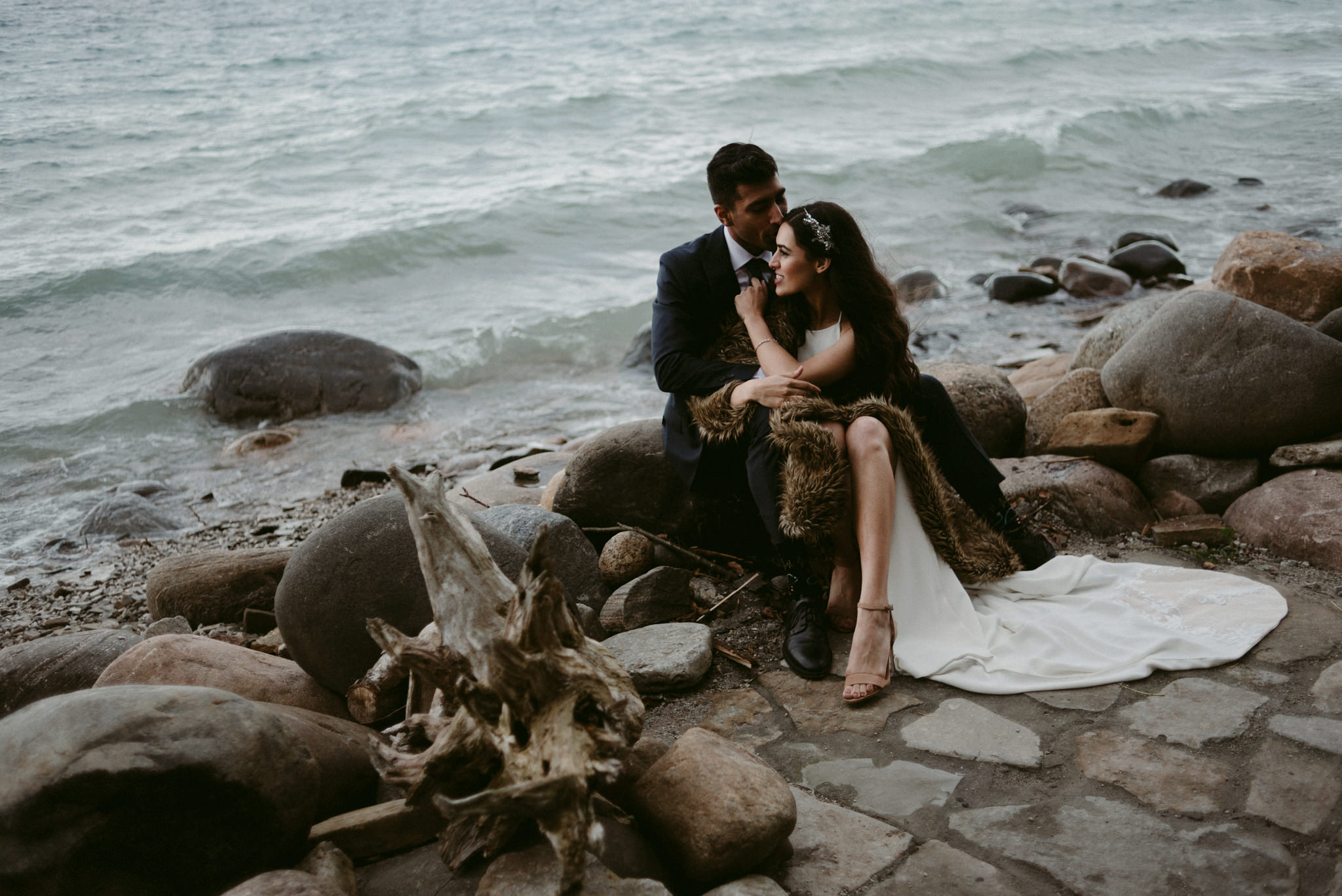 bride and groom sitting on rocks by water