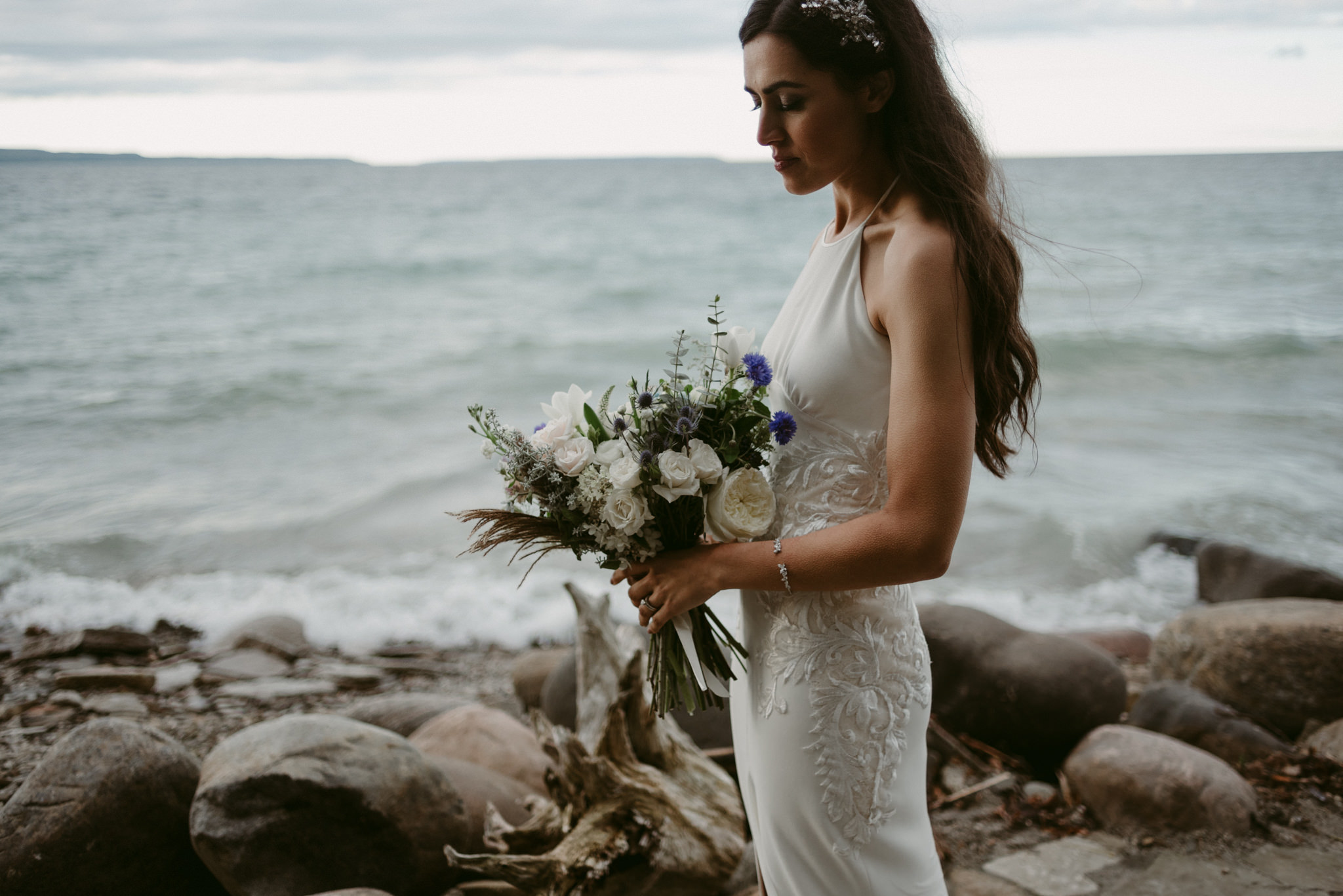 bride holding bouquet by waterfront