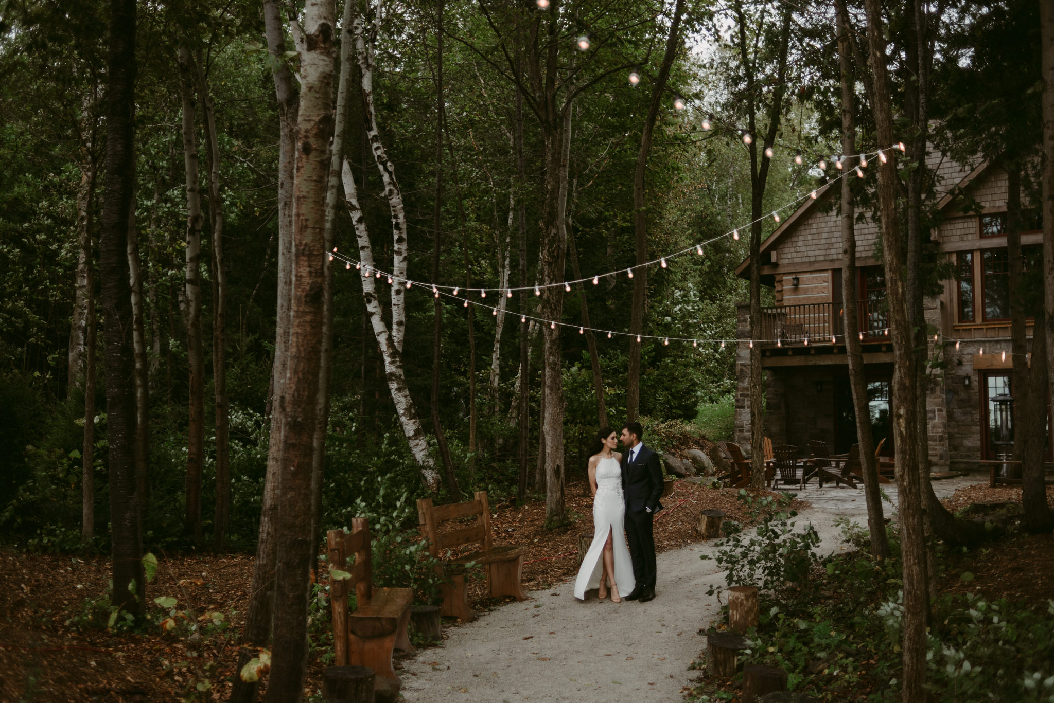 bride and groom under string lights on path behind cottage