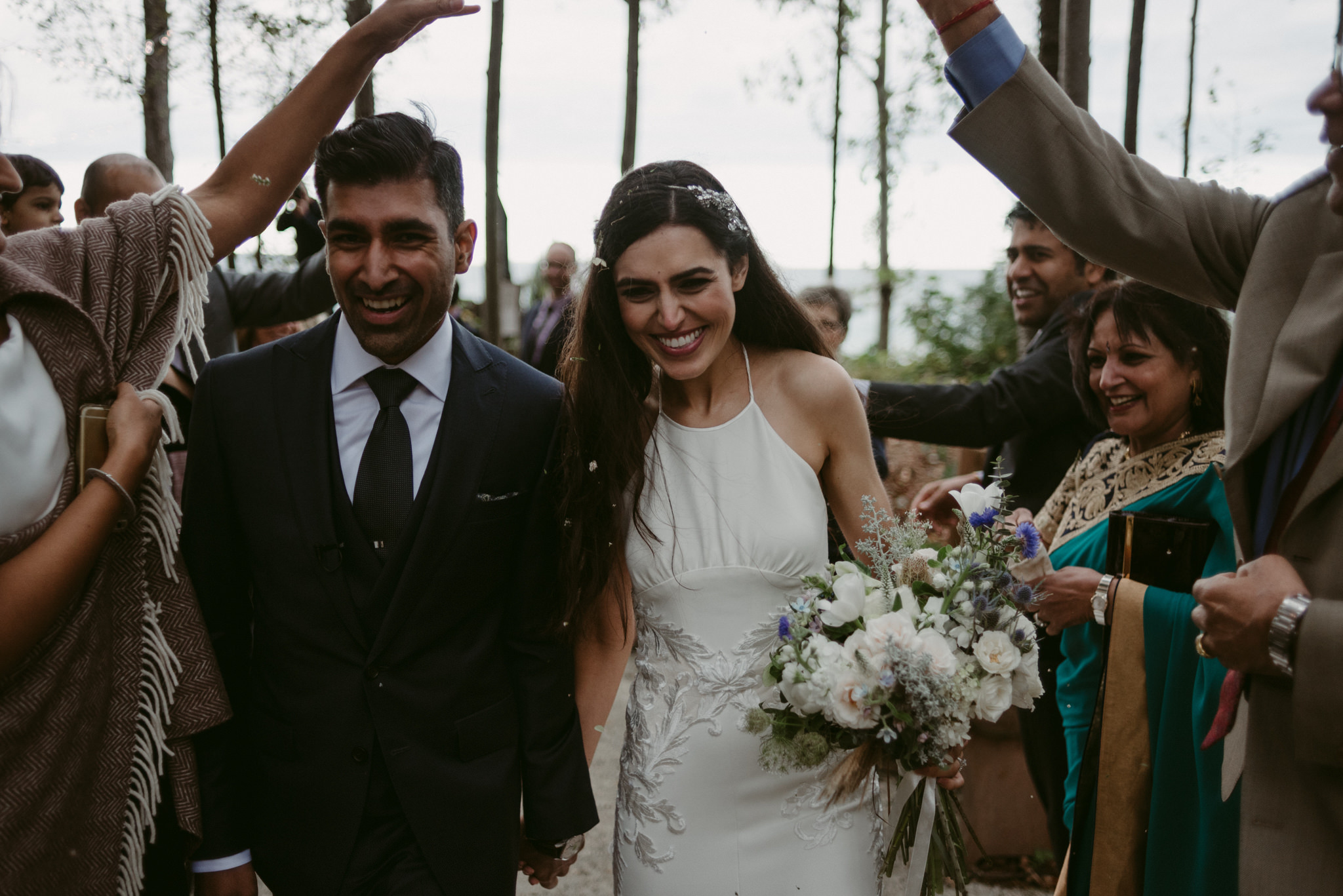 bride and groom showered with flowers during recessional