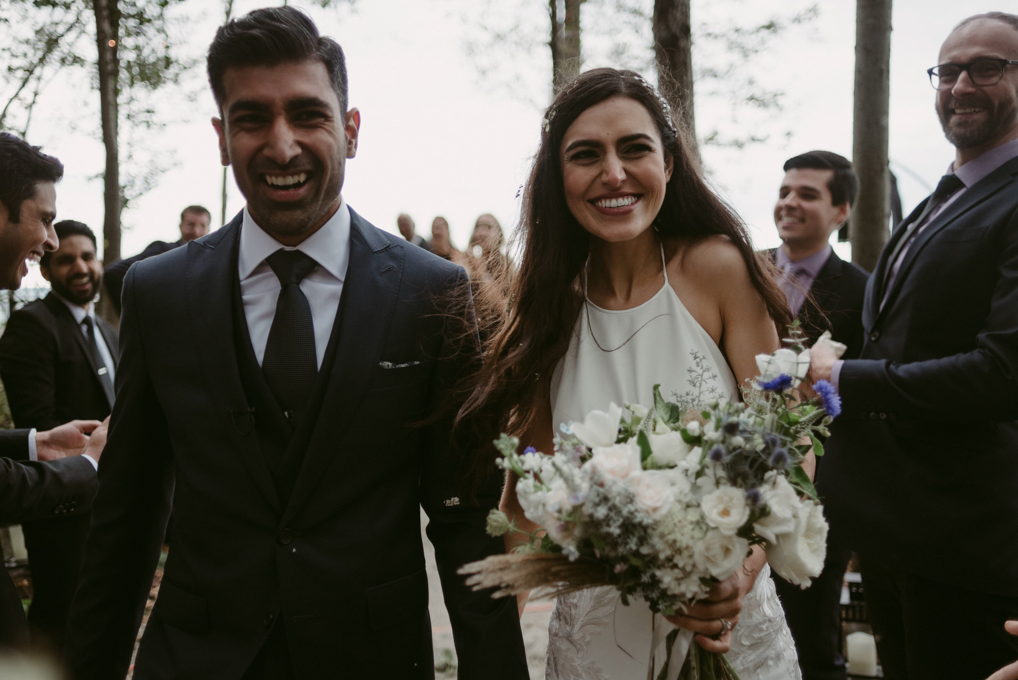 bride and groom showered with flowers during ceremony exit