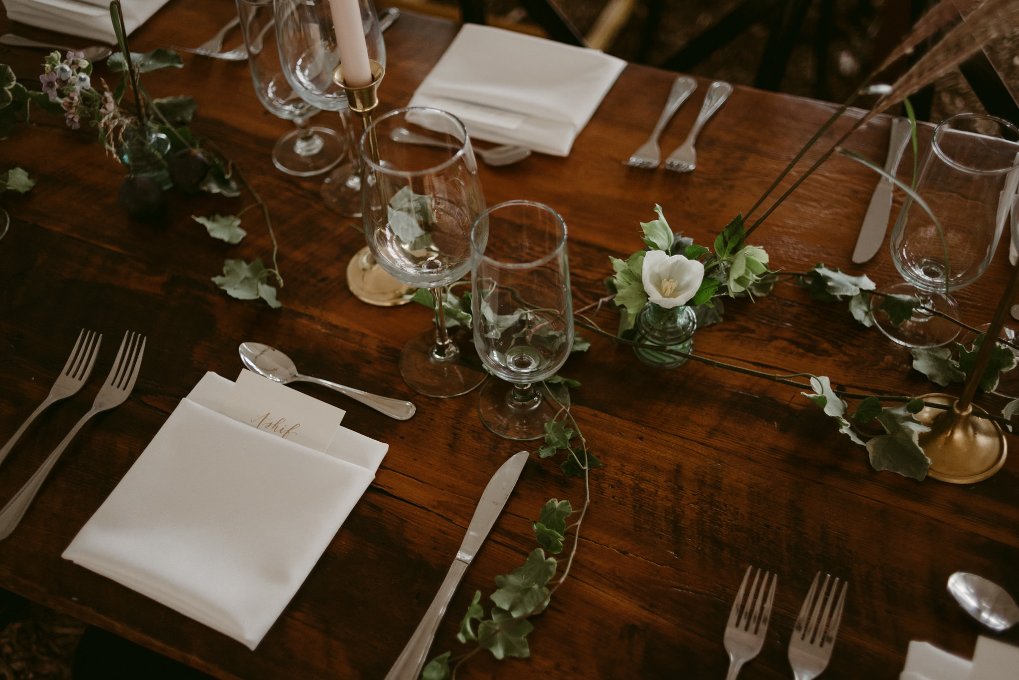 vines and dinnerware on table for wedding reception