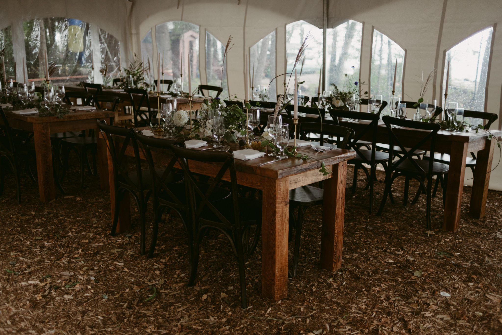 long harvest tables inside tent for wedding reception