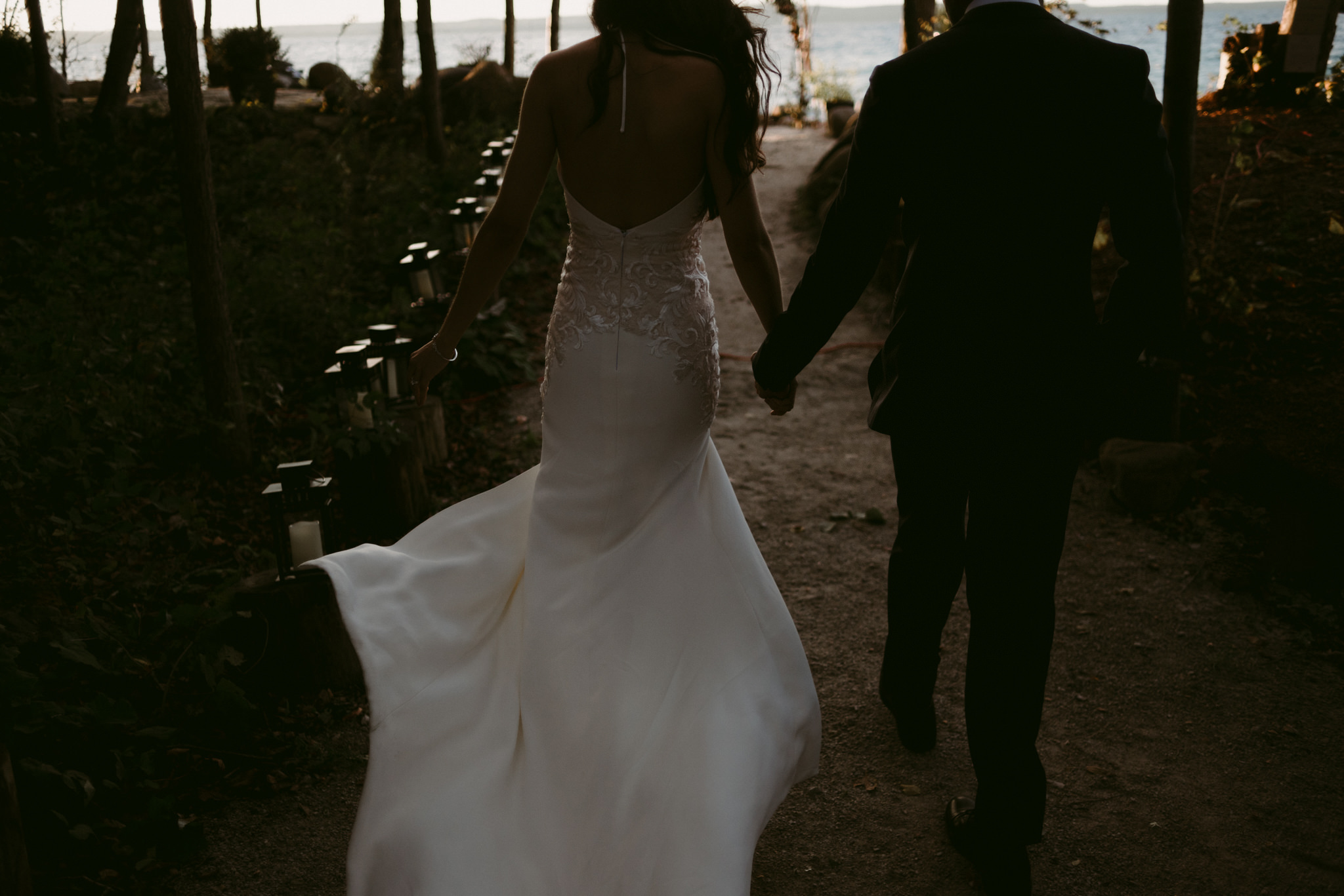bride and groom walking towards water at sunset