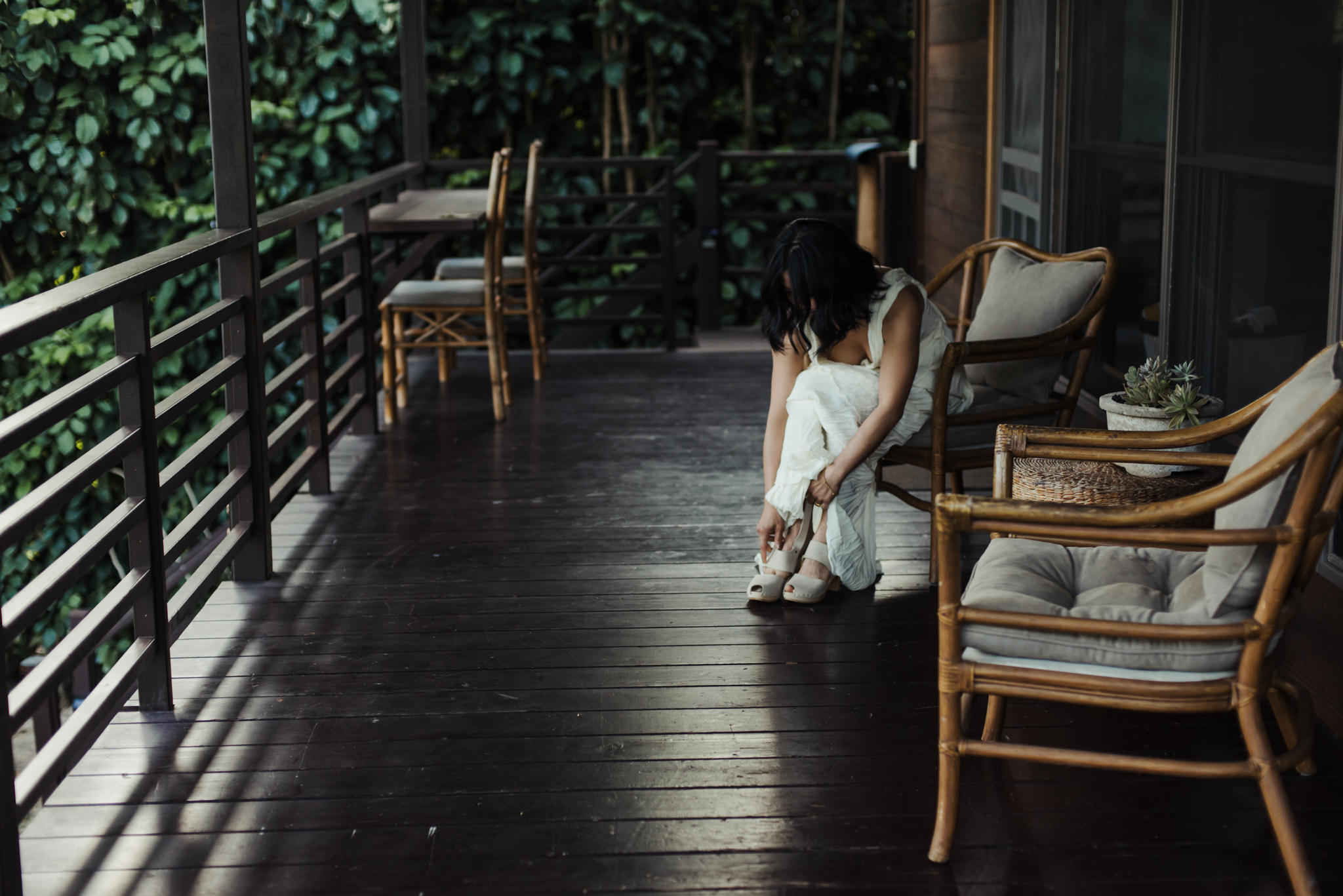 bride putting on shoes on patio outdoors