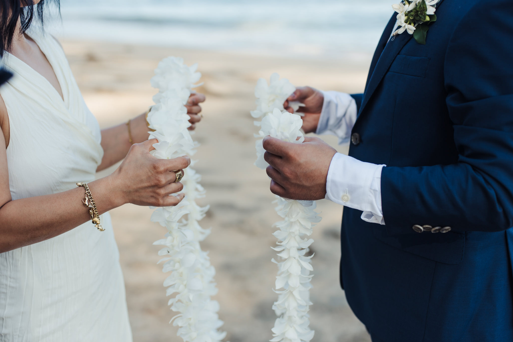 bride and groom holding lei