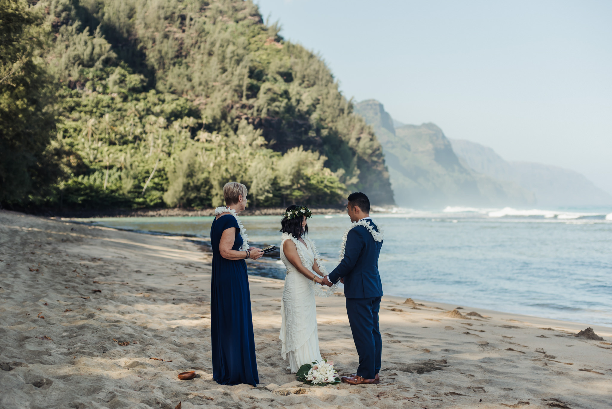 Bride and groom holding hands on beach in Hawaiian wedding ceremony