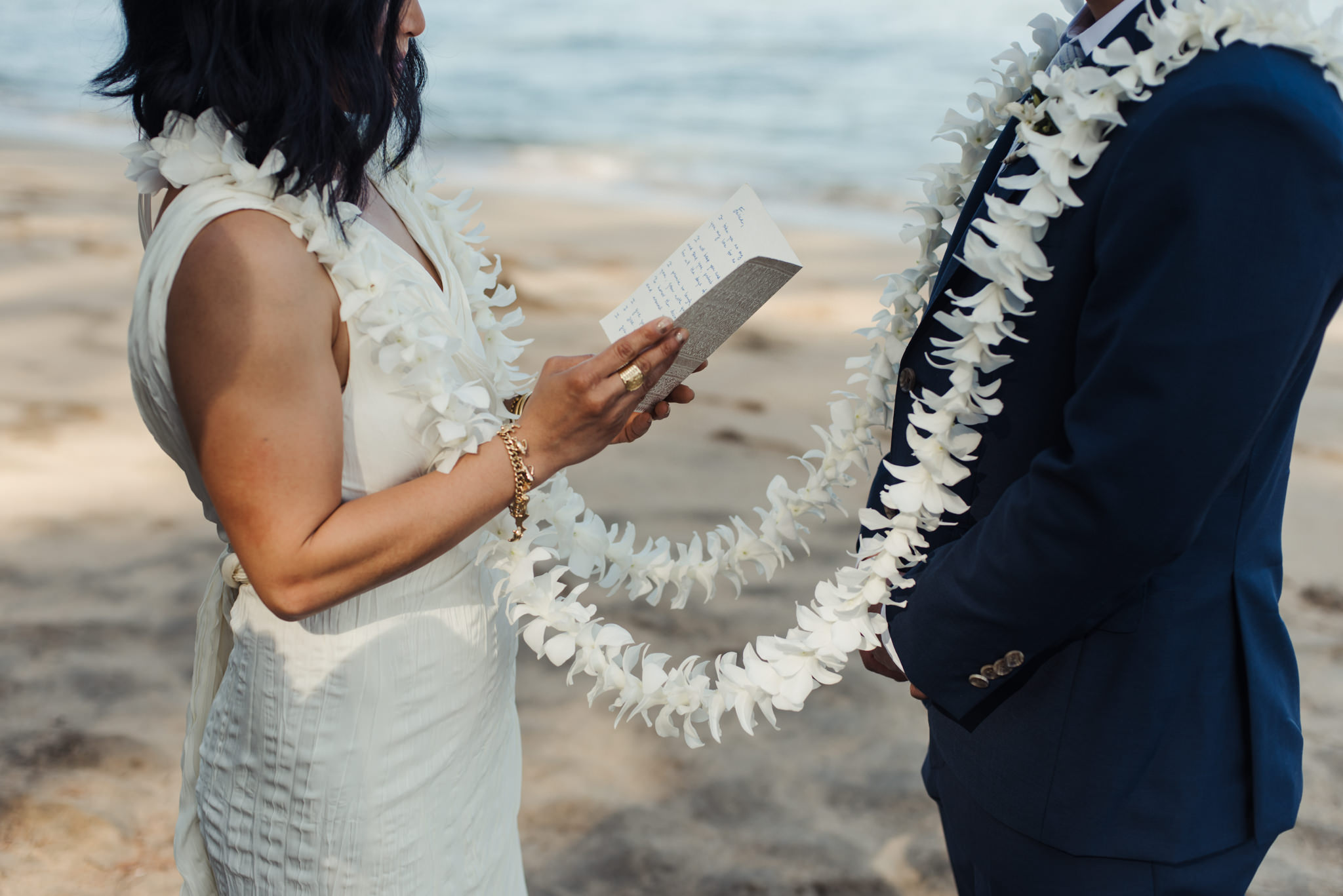 bride reading vows to groom on beach