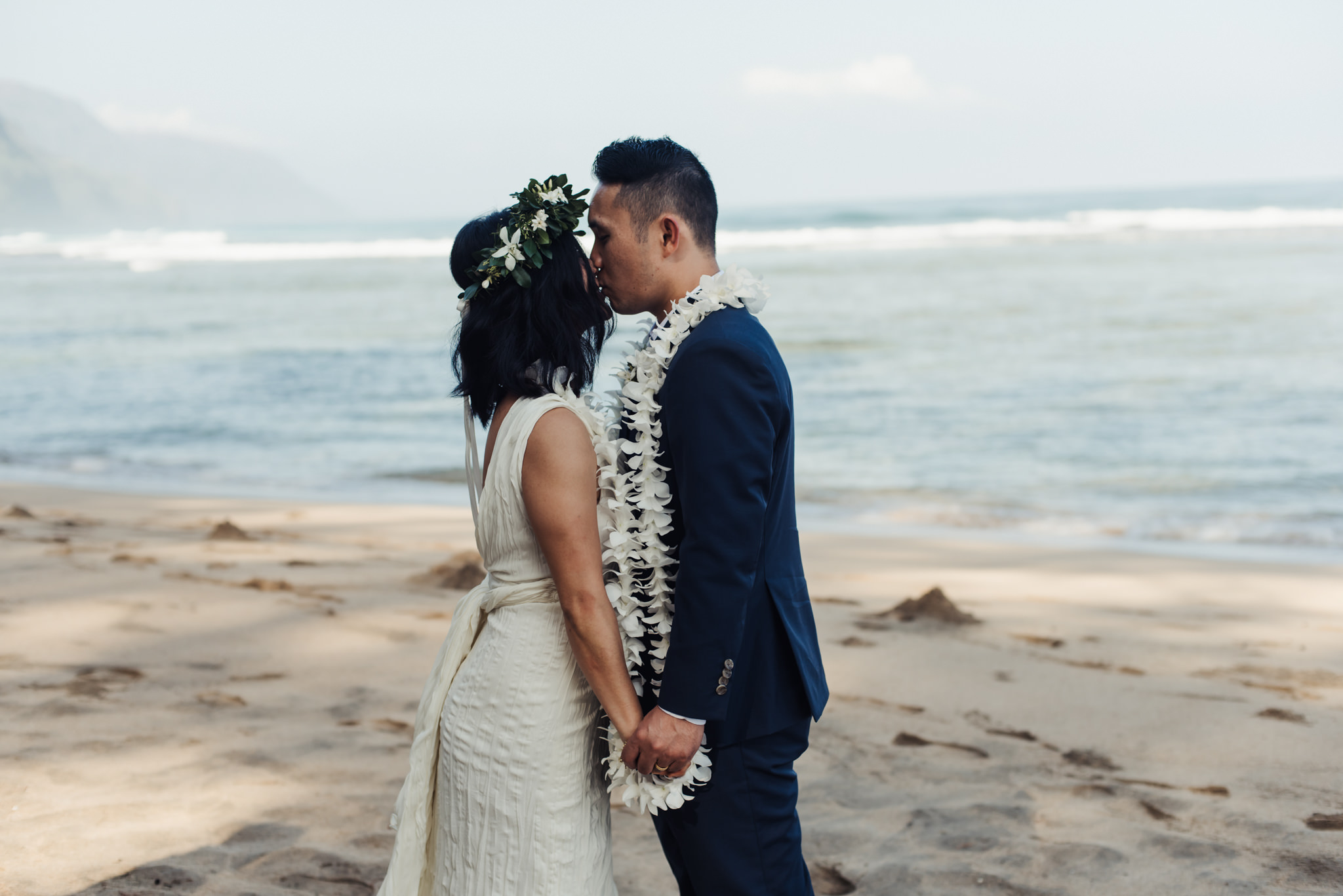 bride and groom kissing on beach in kauai