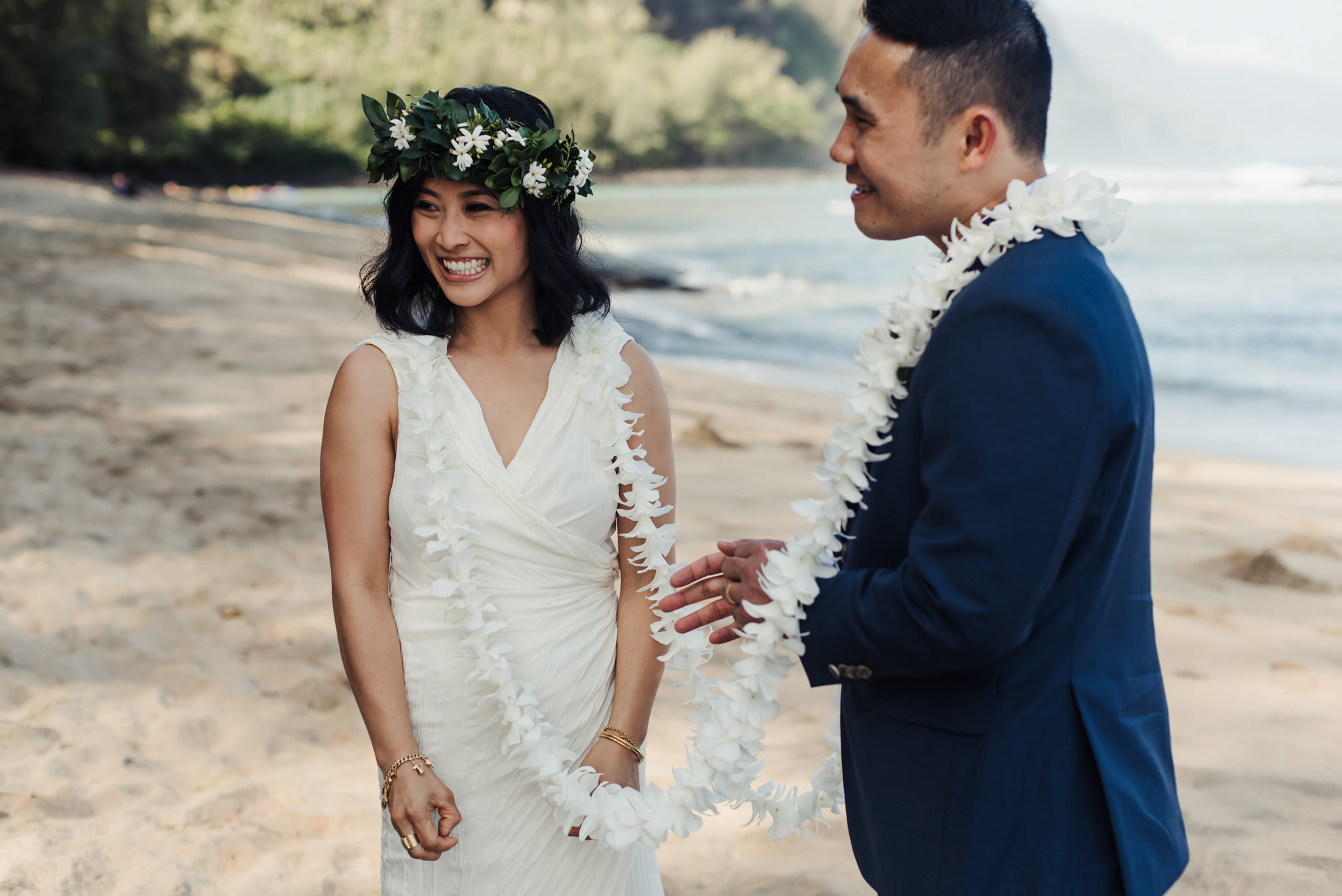 bride and groom smiling during wedding ceremony on beach