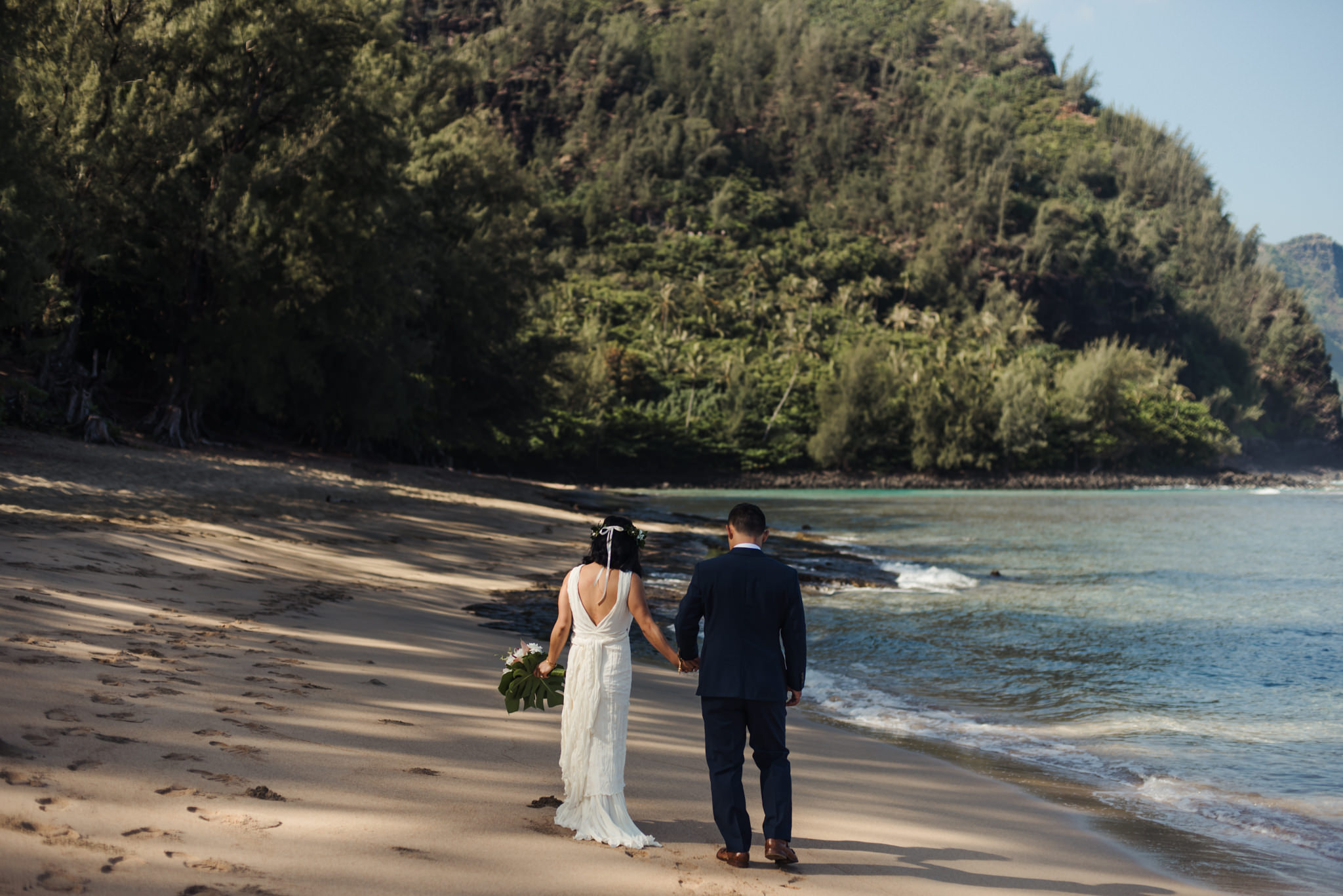 bride and groom walking on beach