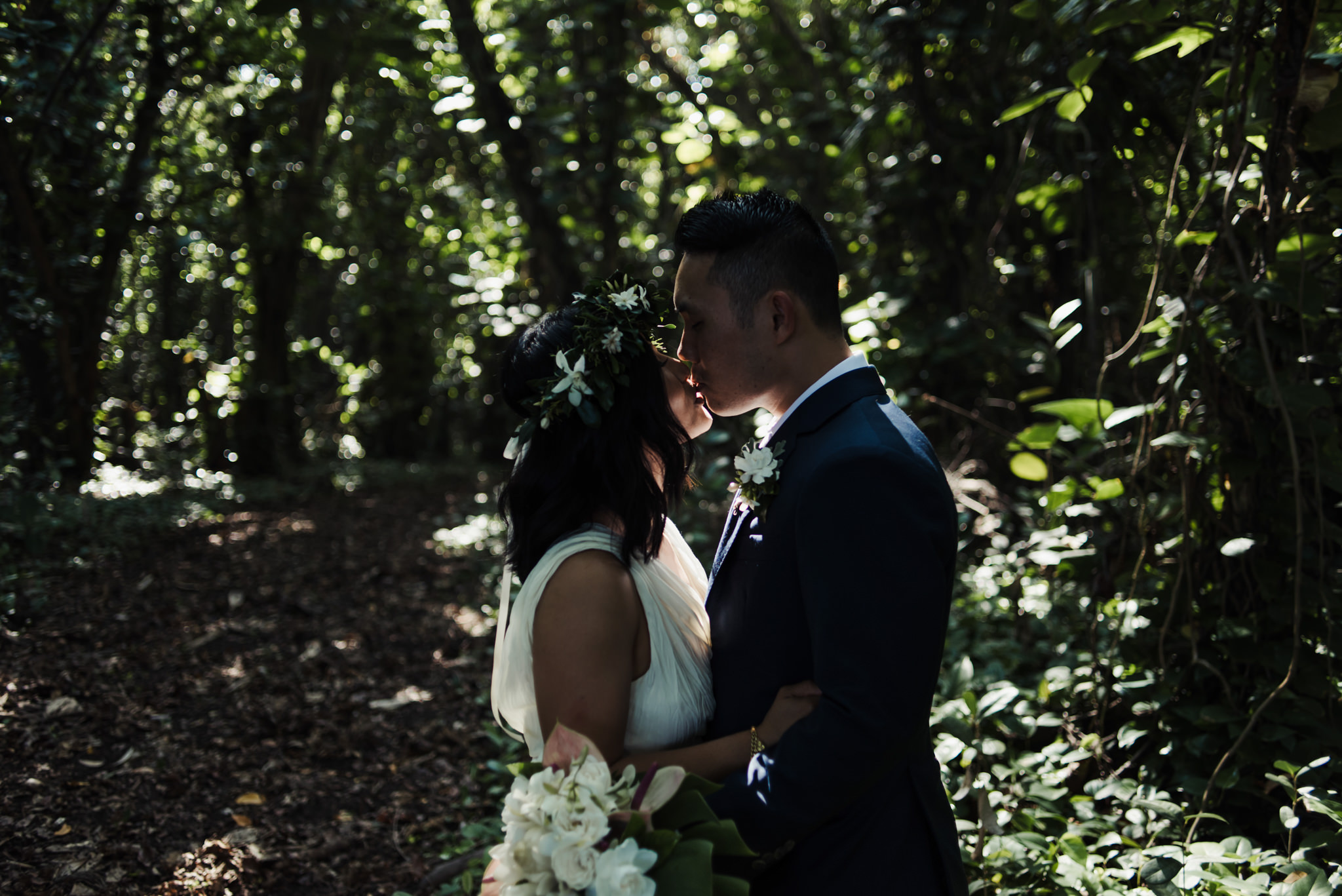 bride and groom kissing in tropical forest