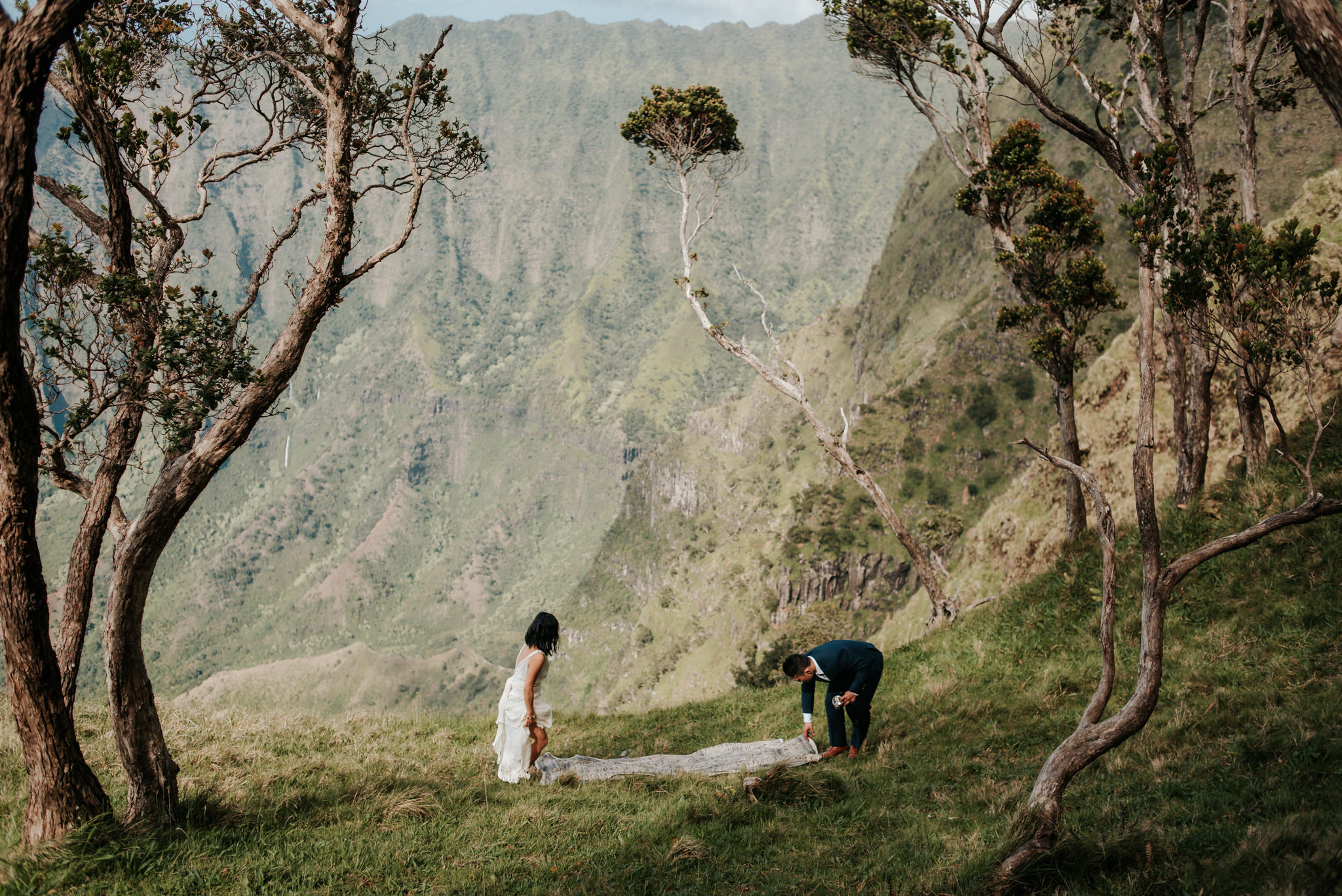 bride and groom setting up picnic with view of Na pali Coast Kauai