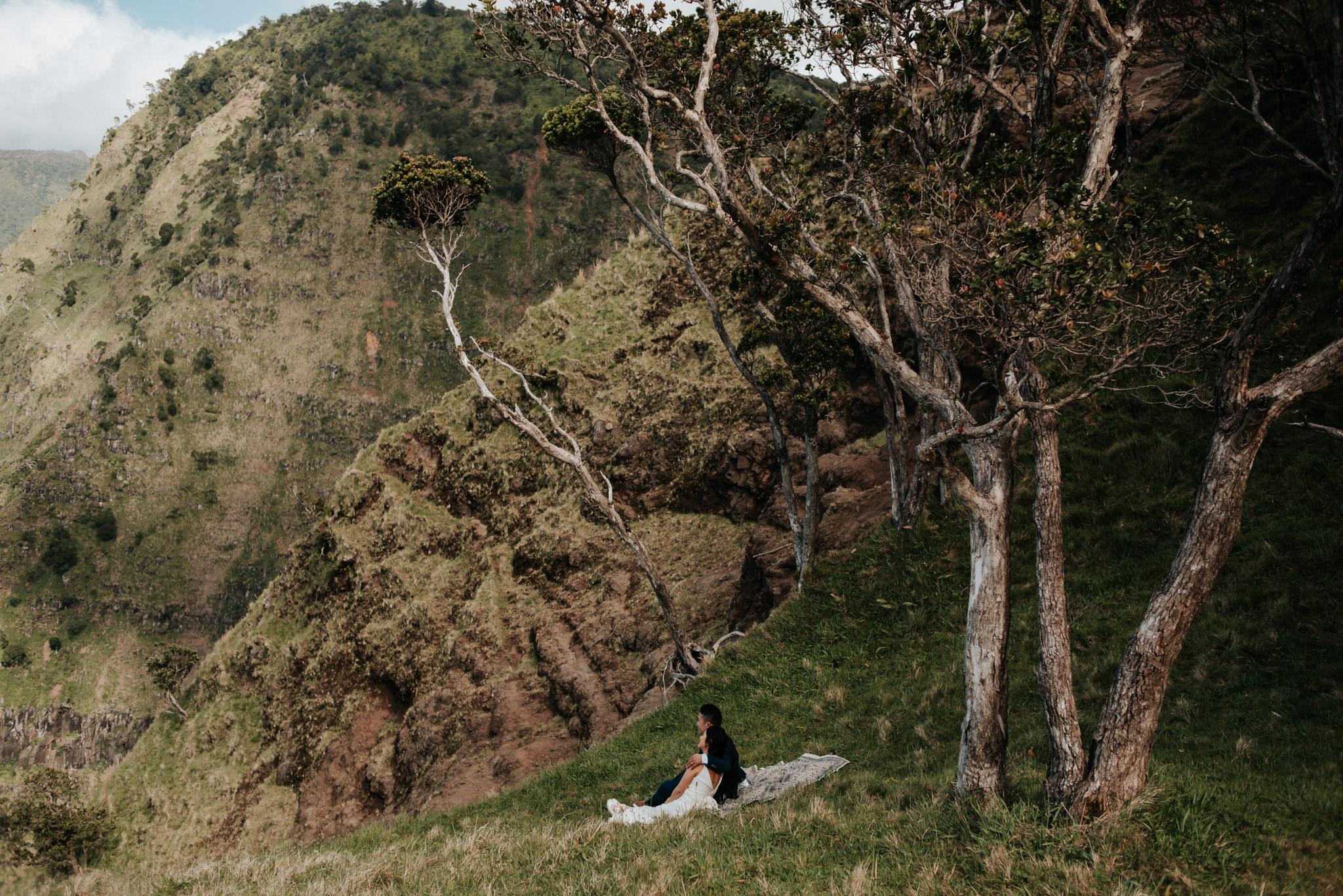 bride and groom having picnic with view of Na pali Coast Kauai