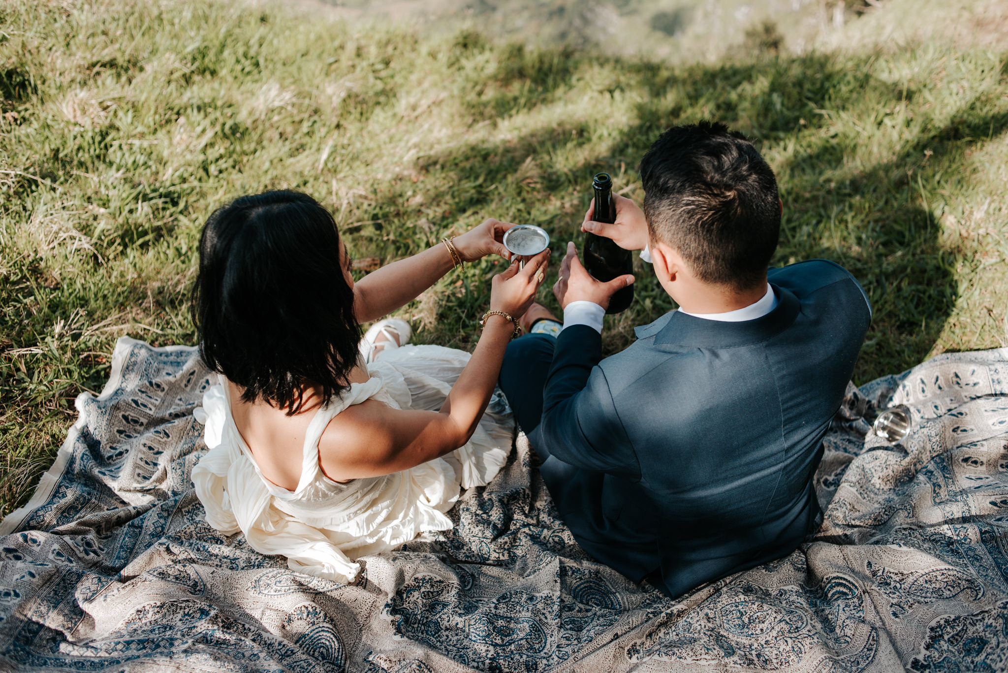bride and groom toasting champagne on picnic blanket