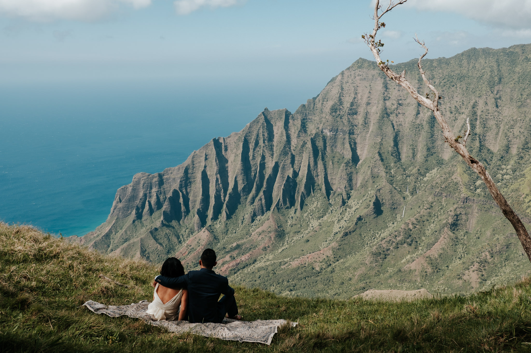 bride and groom sitting on blanket with view of Na pali Coast Kauai