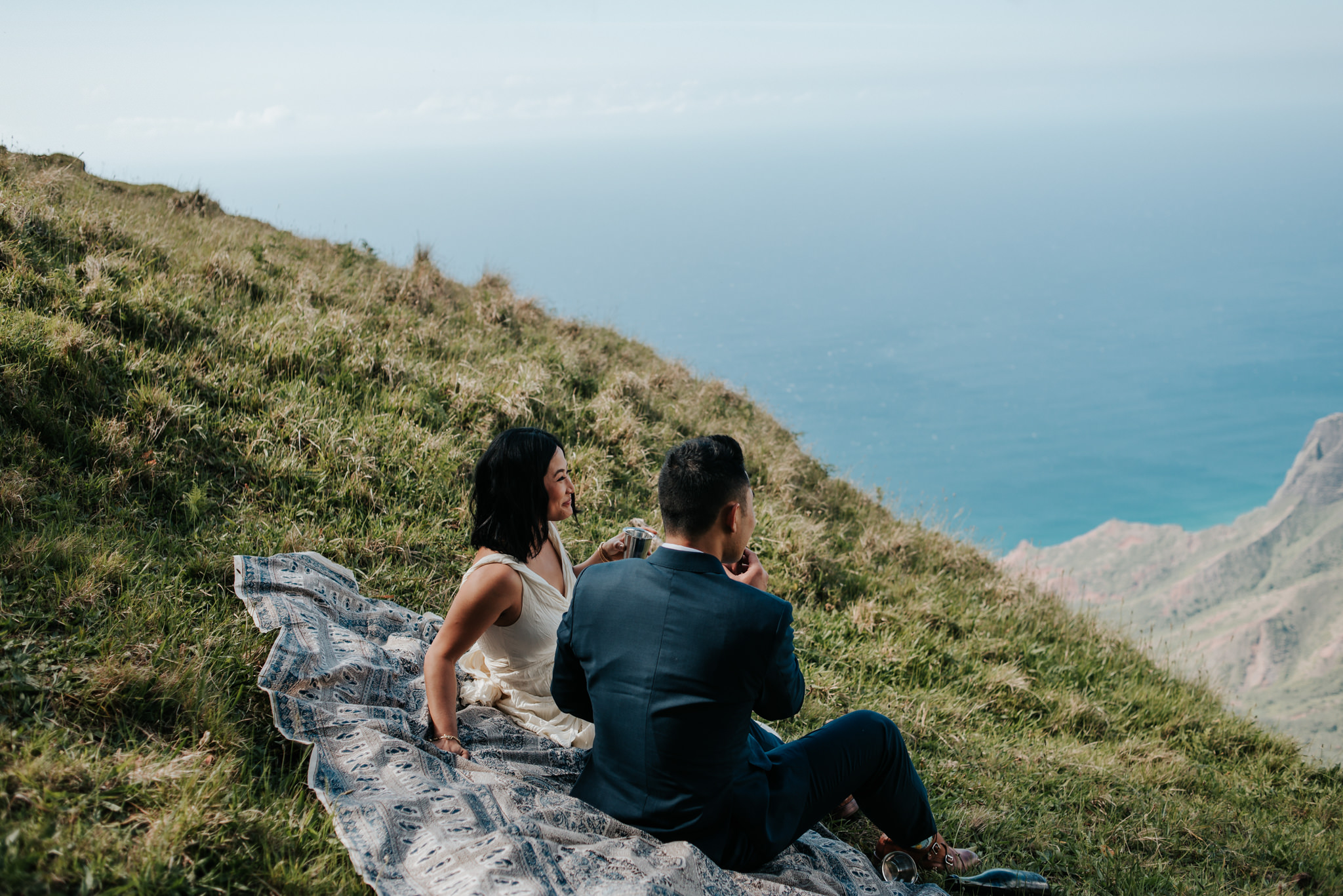 bride and groom toasting champagne on picnic blanket with view of Na pali Coast