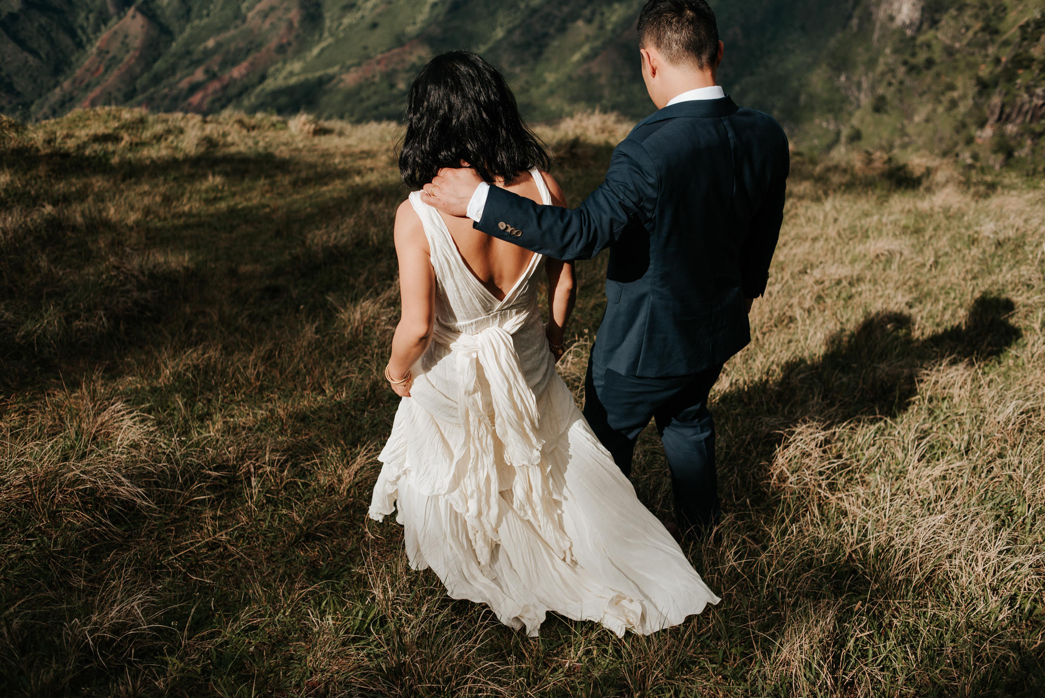 bride and groom walking on cliff edge in kauai