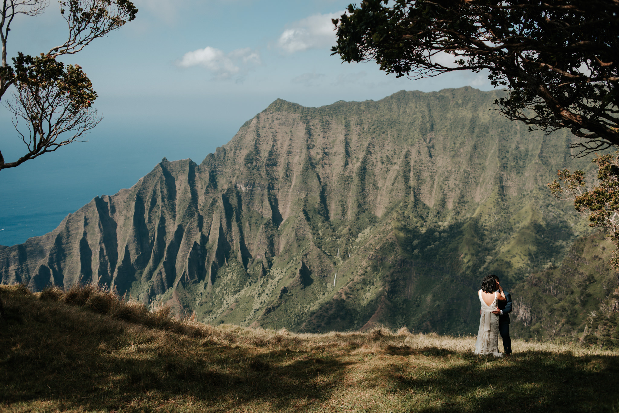 bride and groom hugging with view of na pali coast