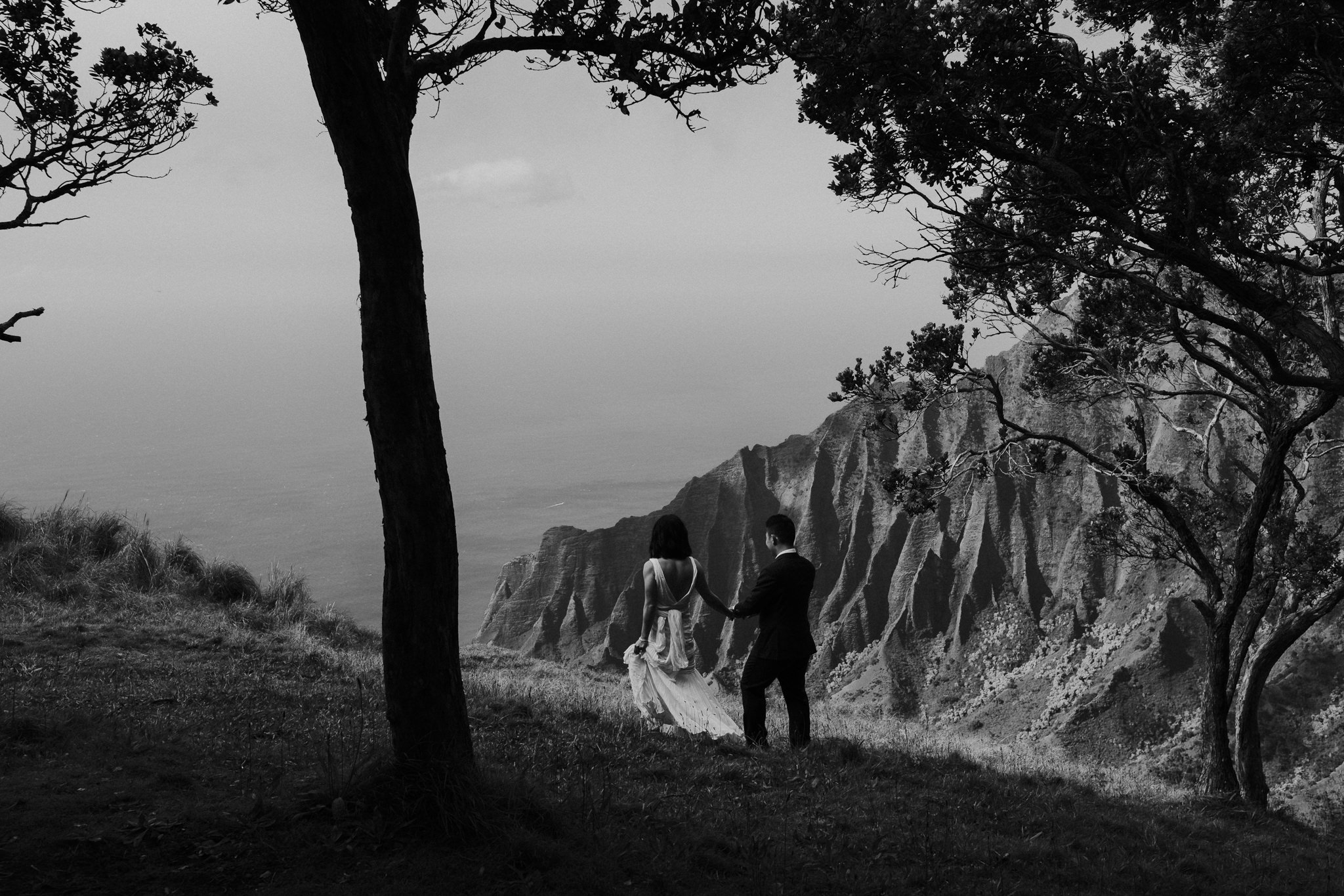 bride and groom walking on cliff edge with view of na pali coast in kauai