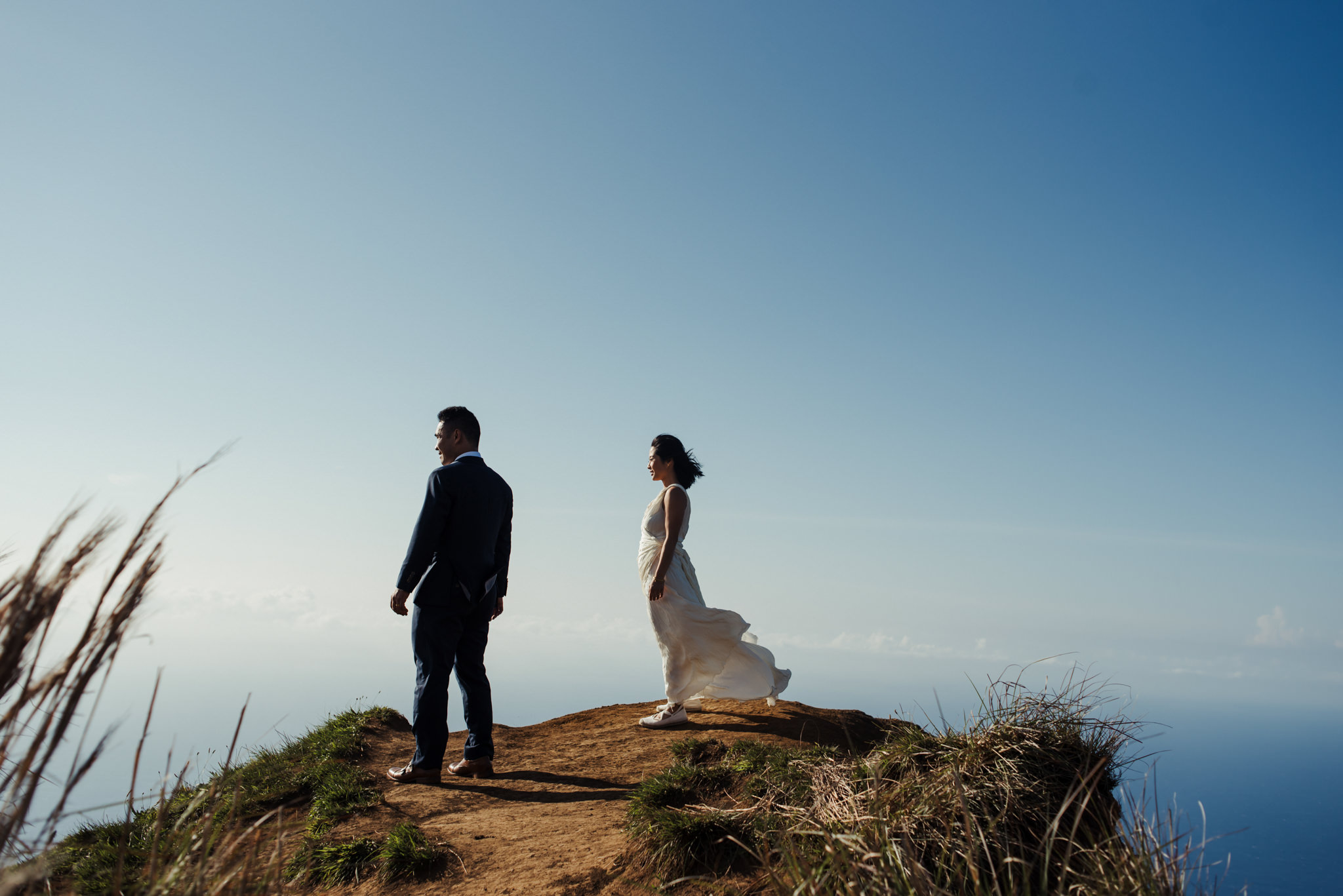 bride and groom on edge of cliff in kauai