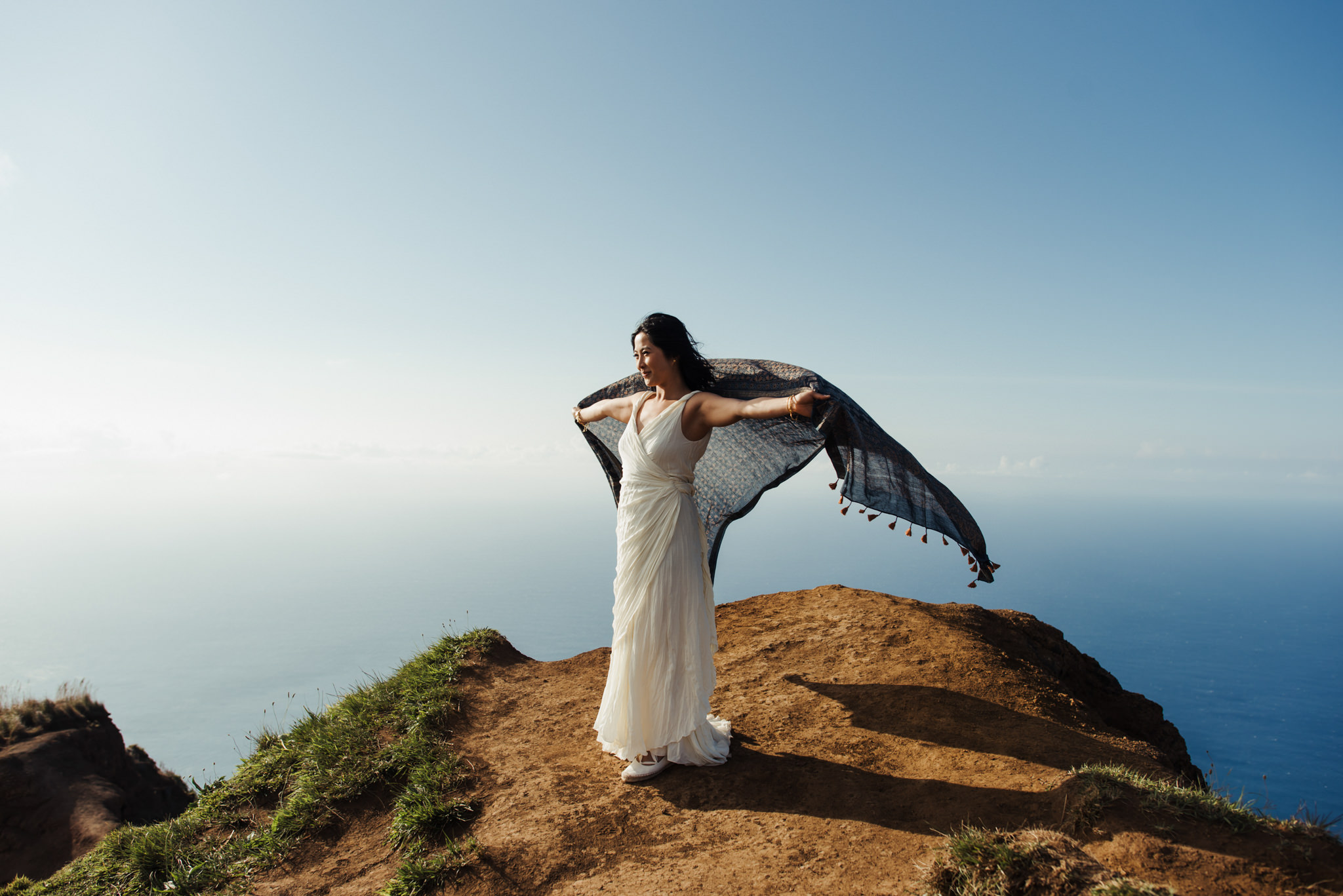 bride holding up scarf on edge of cliff as it floats in wind