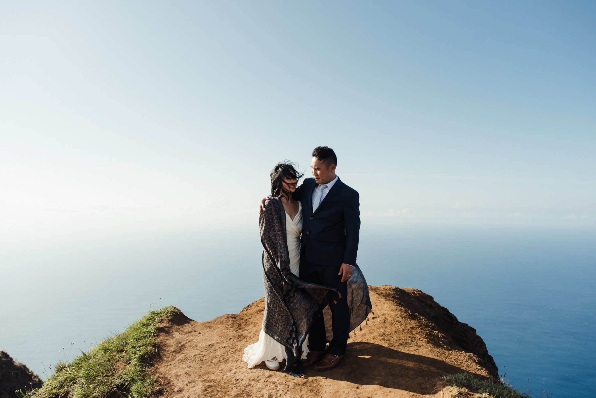 bride wrapped up in scarf on edge of cliff in Kauai