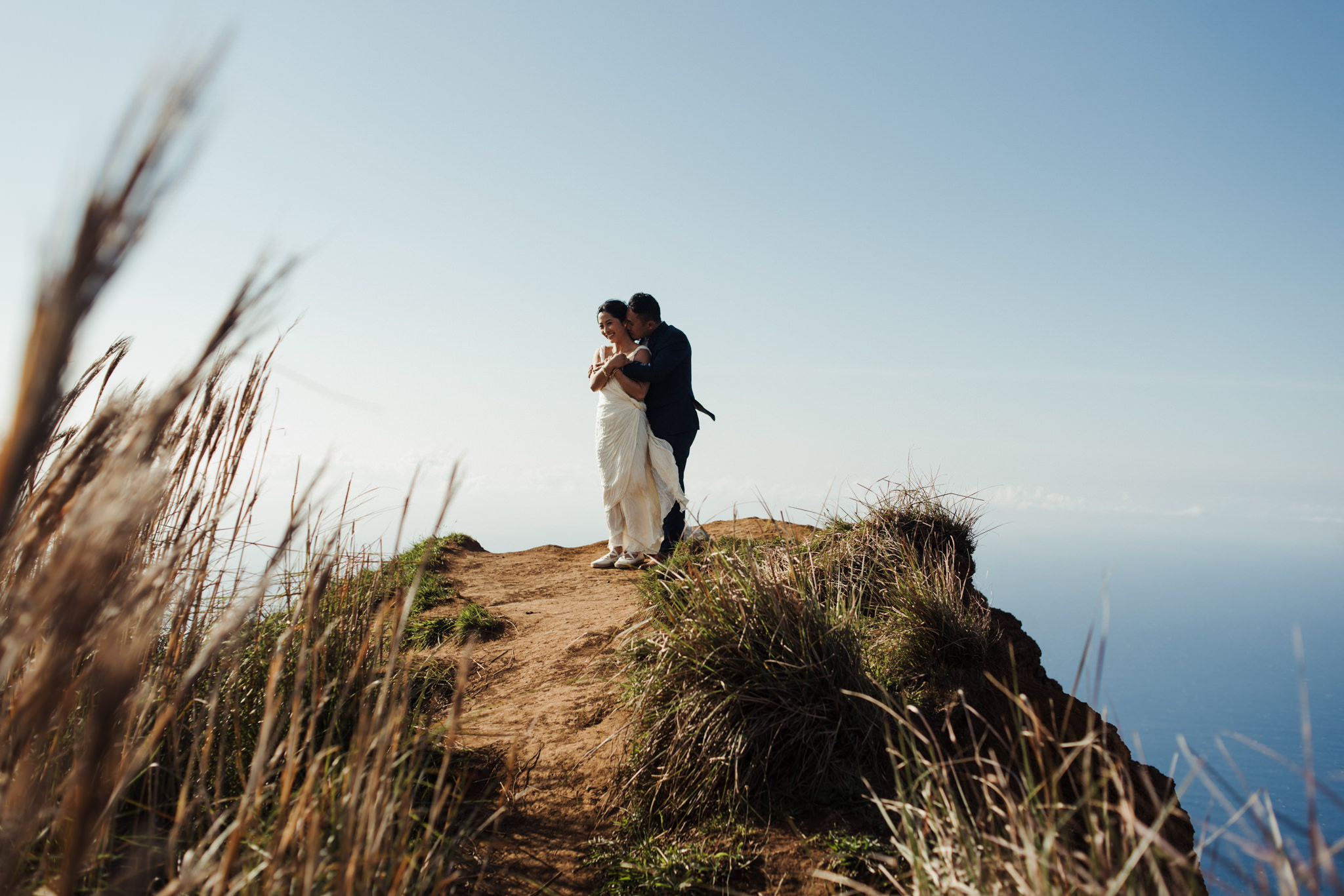 Bride and groom hugging on edge of cliff at top of Na Pali coast in Kokee State Park